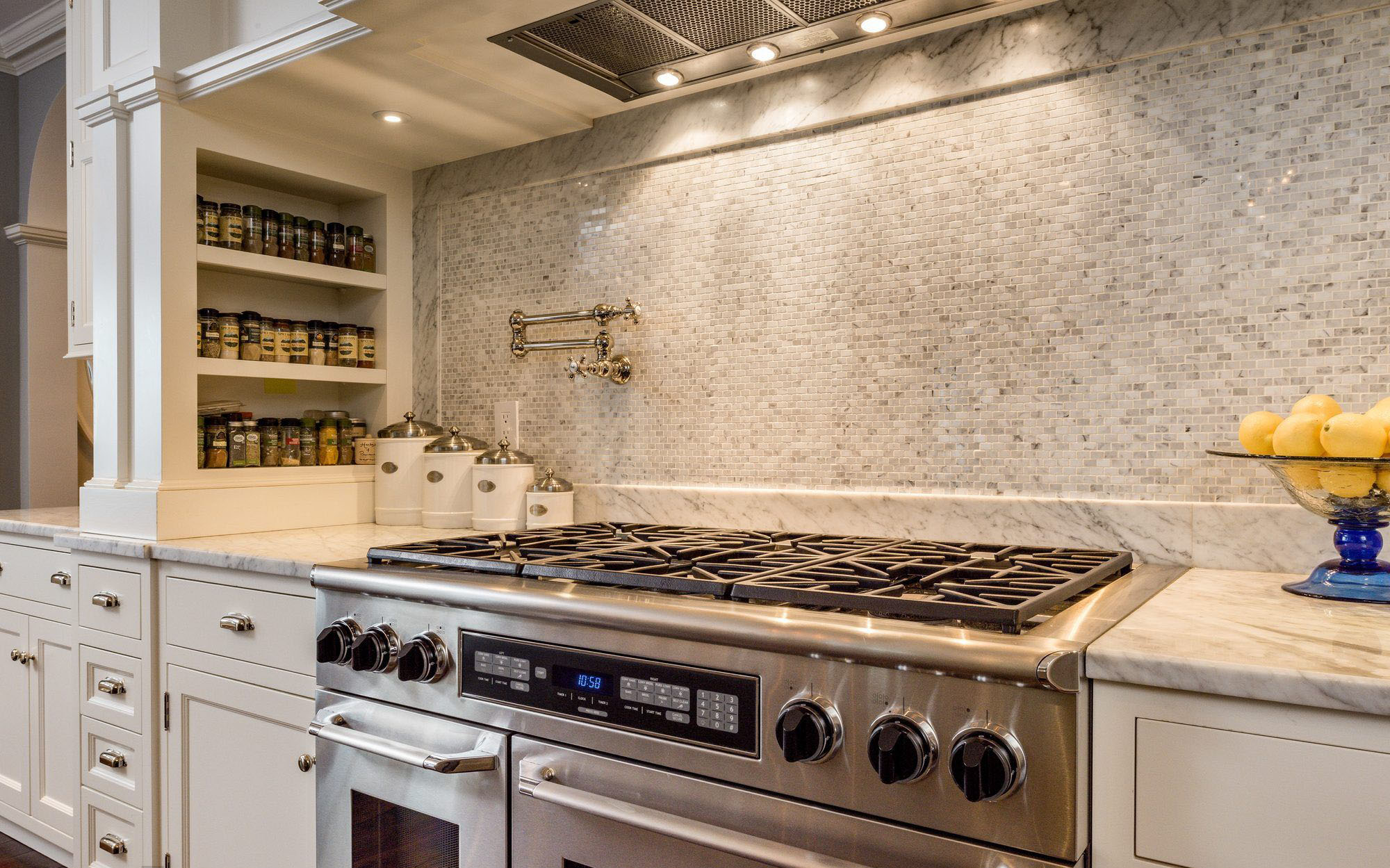 Closeup view of a beautiful stove backsplash made from rectangular marble tiles. built in spice rack.