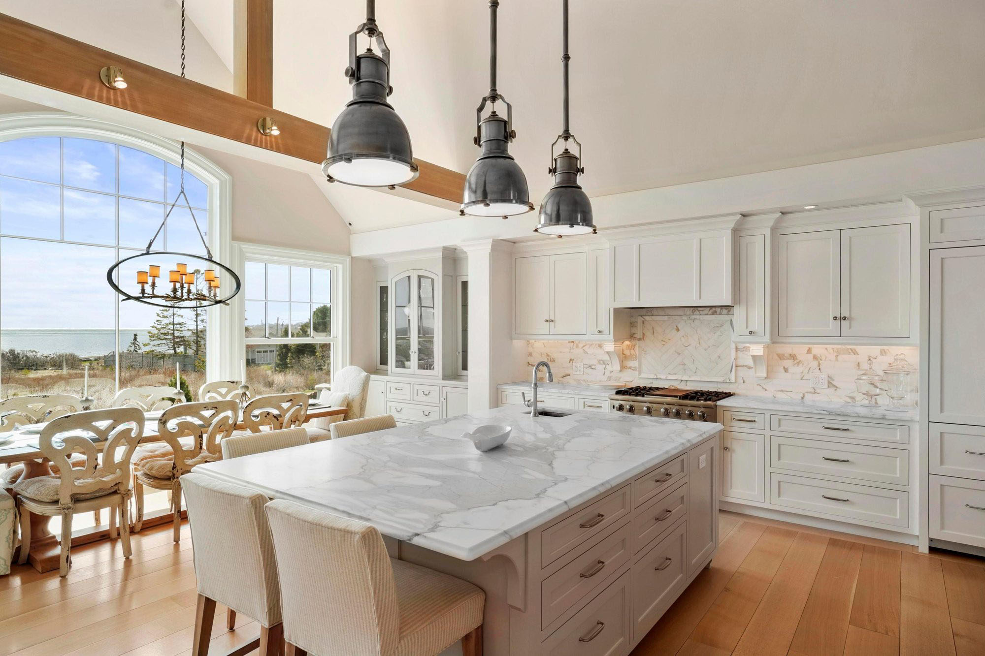 White shaker style kitchen cabinets with a matching island, marble countertops, industrial style pendant lighting and exposed ceiling beams.