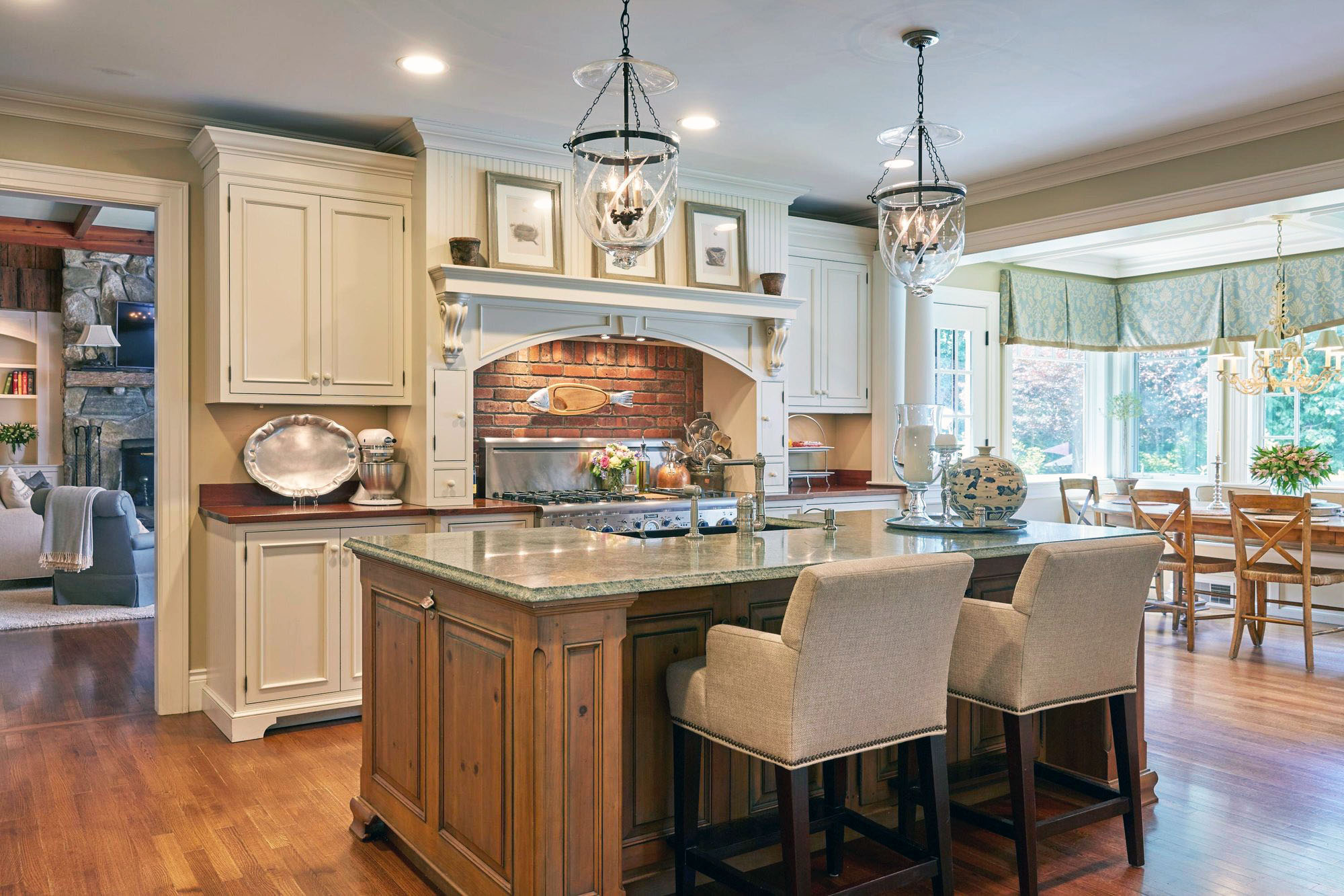 Country kitchen design using real stained wood, a red brick backsplash and granite countertops.