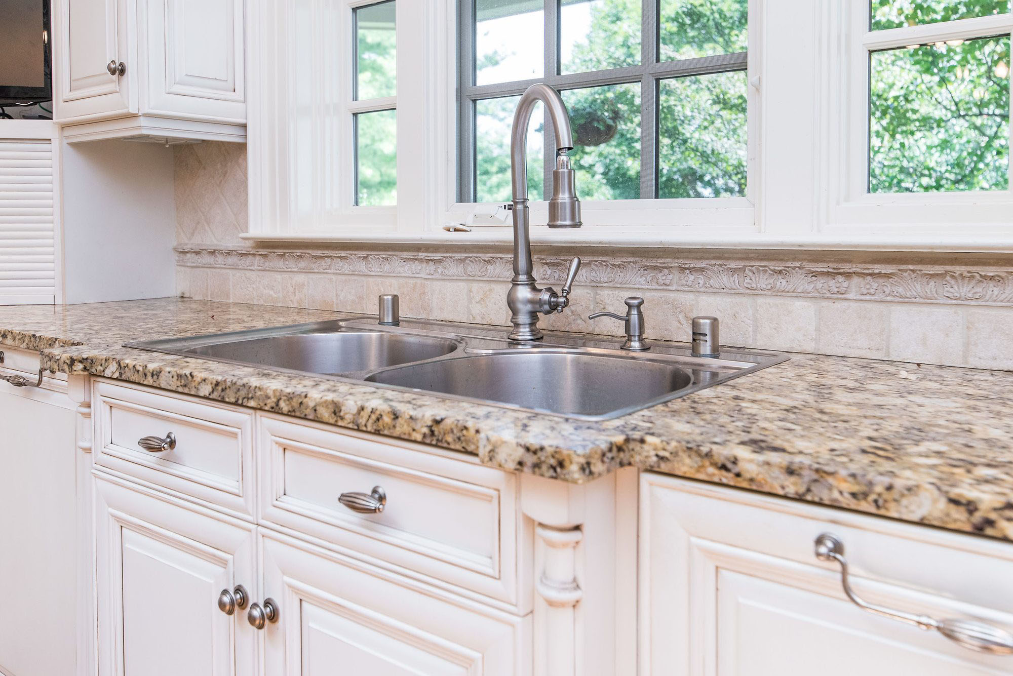 Closeup view of a stainless steel double basin sink on granite countertops.