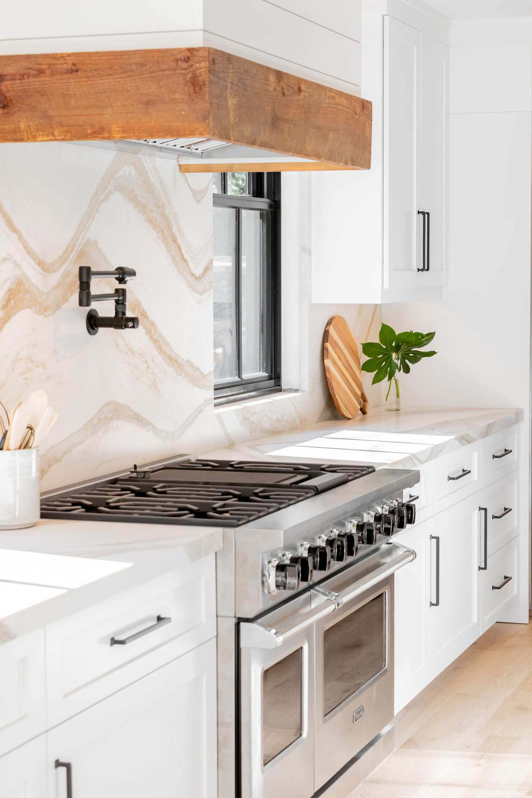 Closeup view of a beautiful luxury kitchen featuring solid marble slab counters and backsplash, Viking range and custom wood trimmed hood.