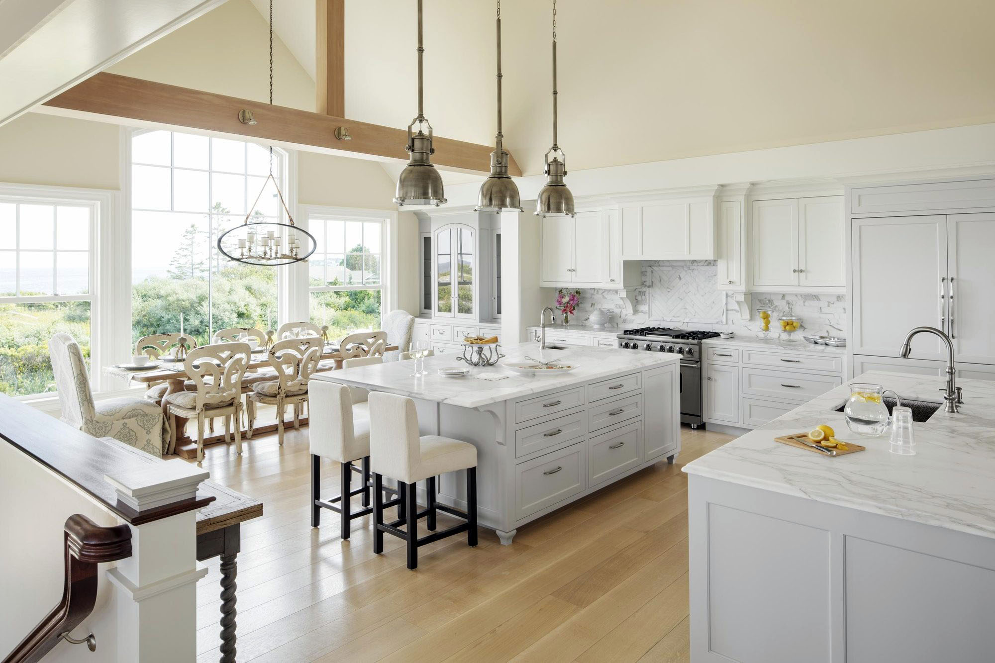 Open concept luxury kitchen with a large island flowing to a dining area with 8 seat wood table.