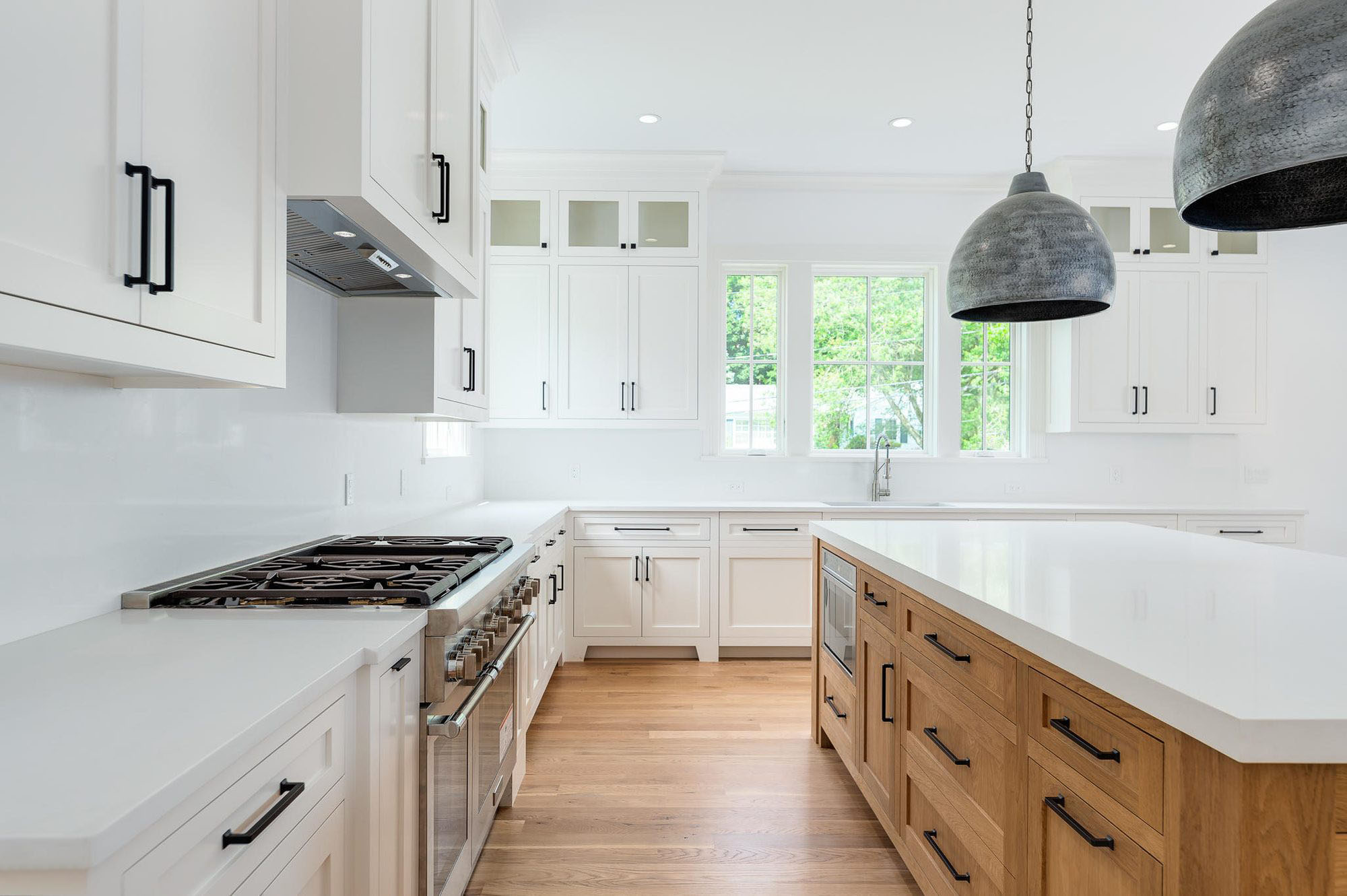 White shaker style cabinetry with a white quartz solid slab backsplash and natural wood island.