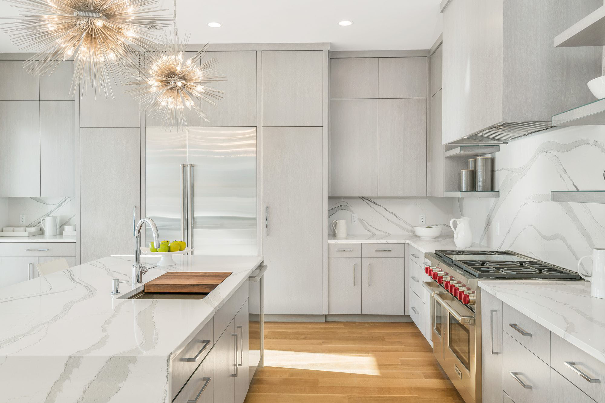 Modern kitchen design with marble quartz countertops, solid slab backsplash and flat faced light gray cabinets.