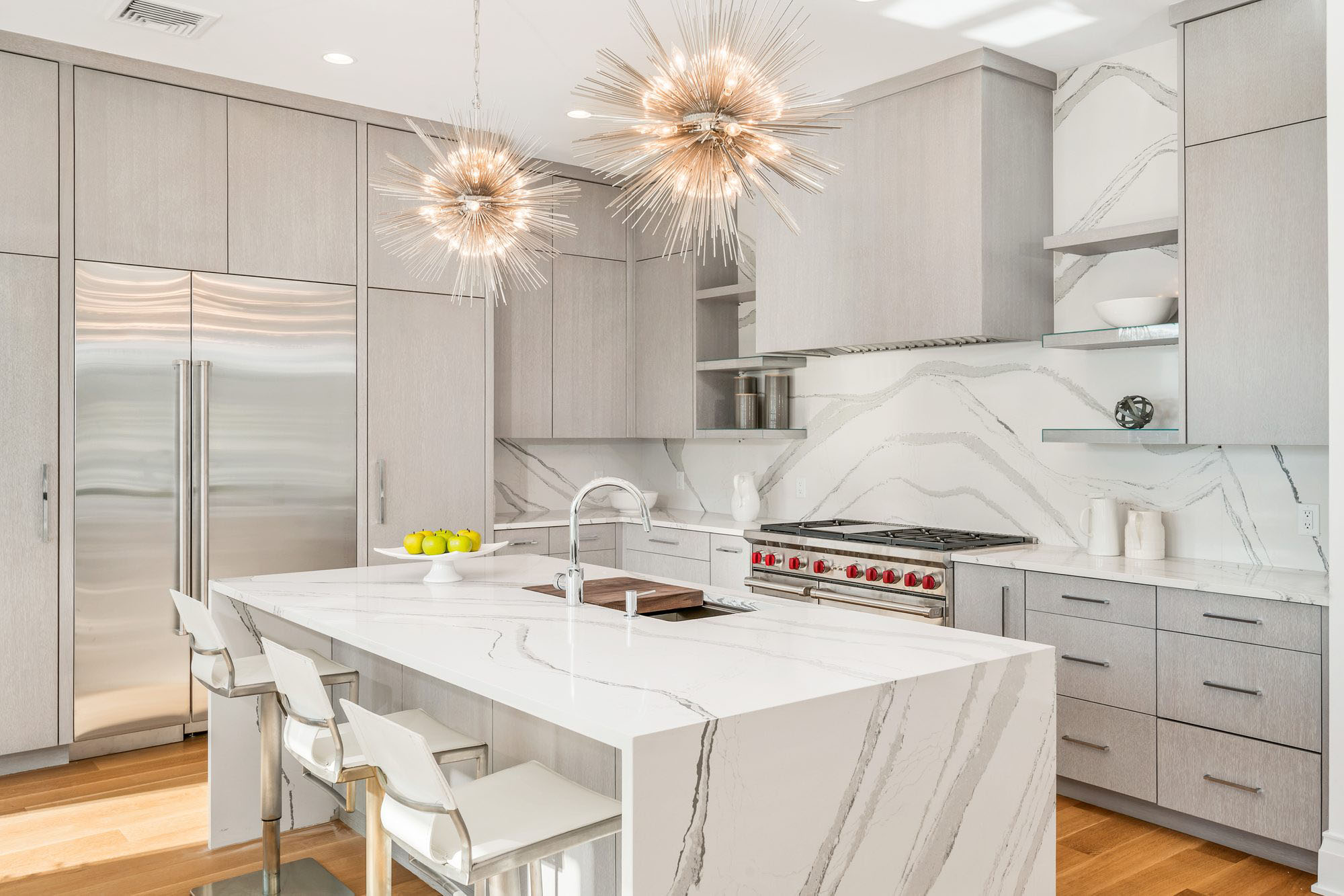 beautiful modern kitchen with marble quartz countertops and matching solid slab backsplash, flat faced light gray cabinets. Wolf stove with red knobs.