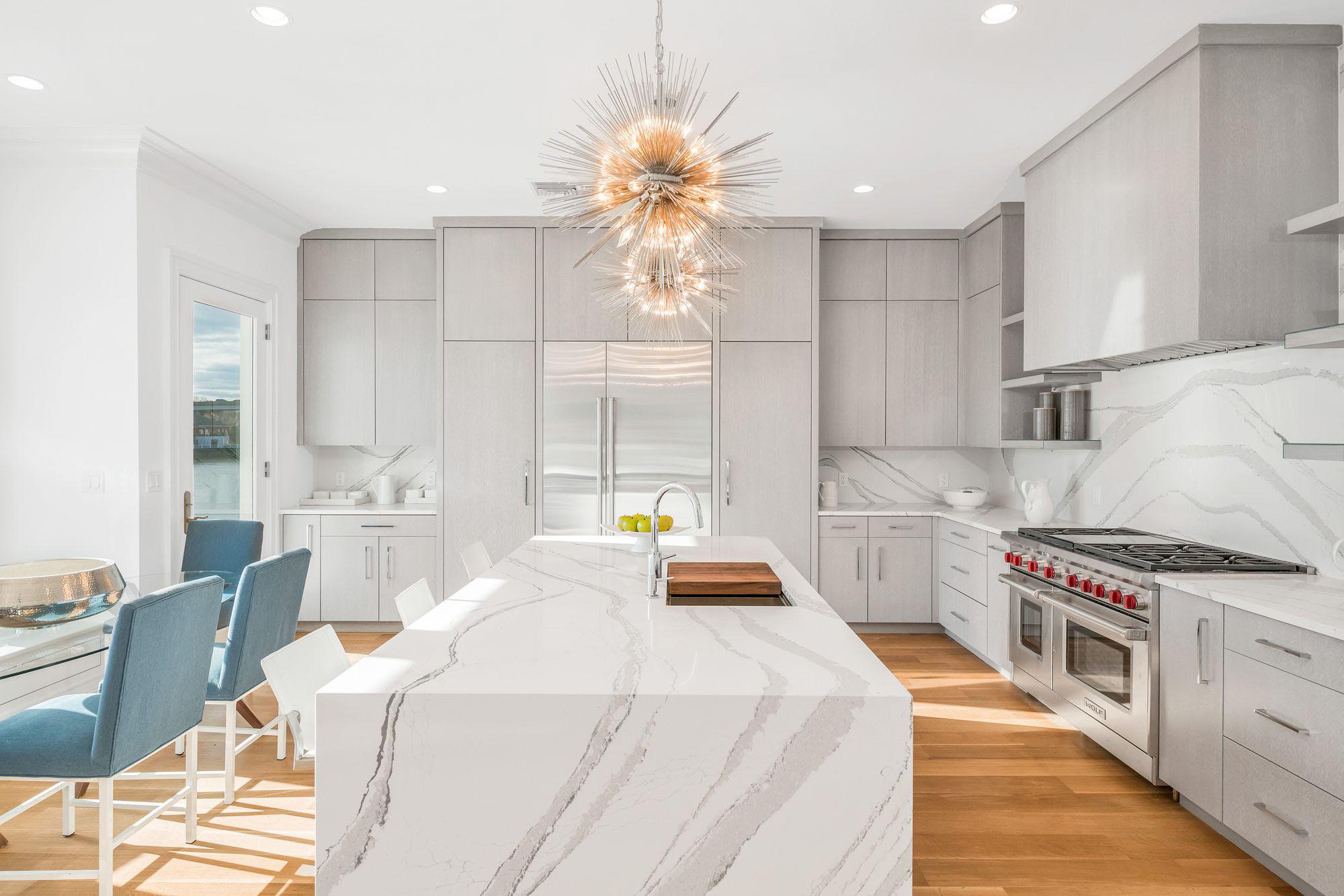 modern kitchen, marble quartz countertops, solid slab backsplash, cool pink pendant lighting, wolf stove red knobs