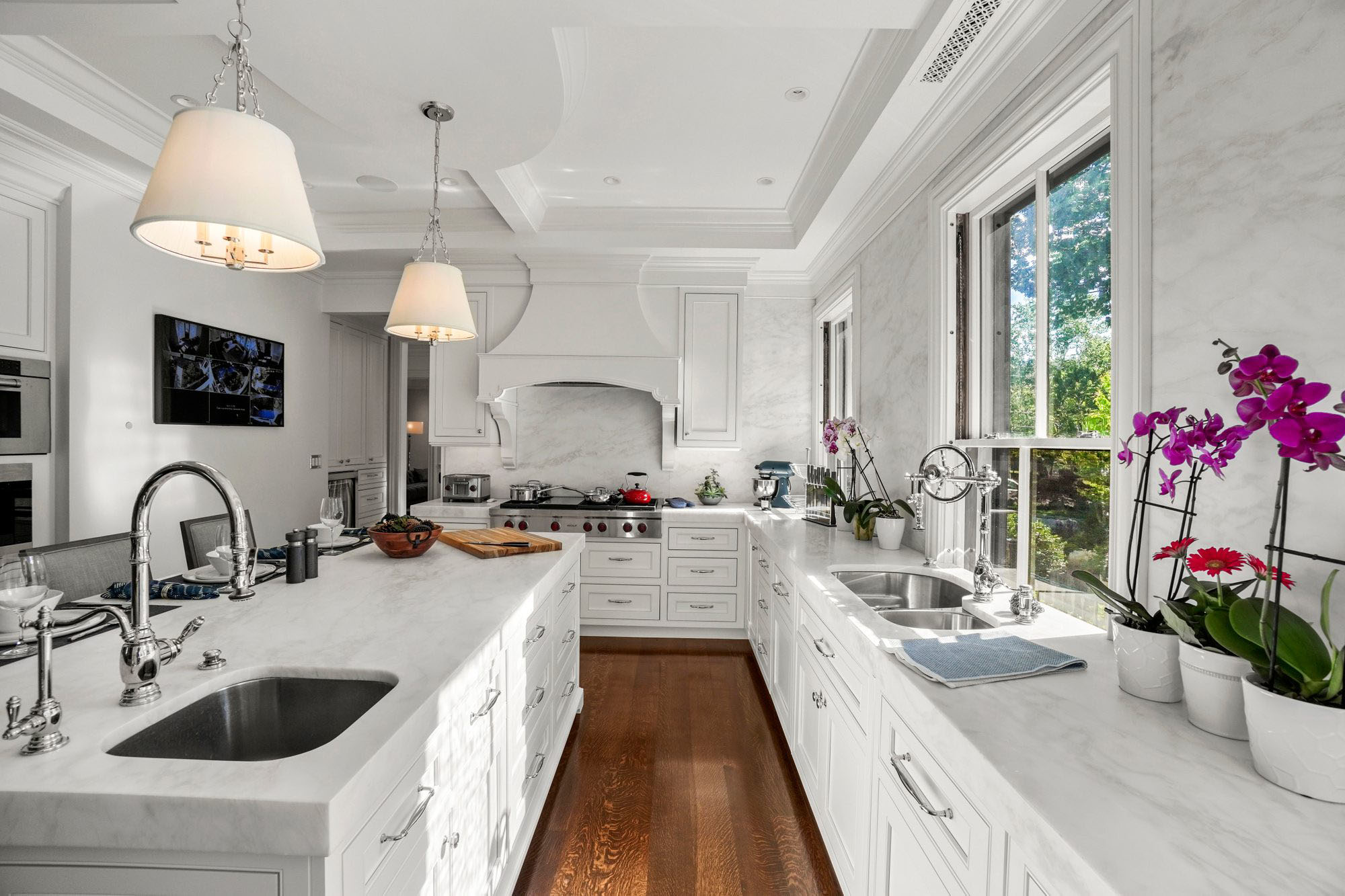 White and marble kitchen with rich brown hardwood floors. Custom range hood.