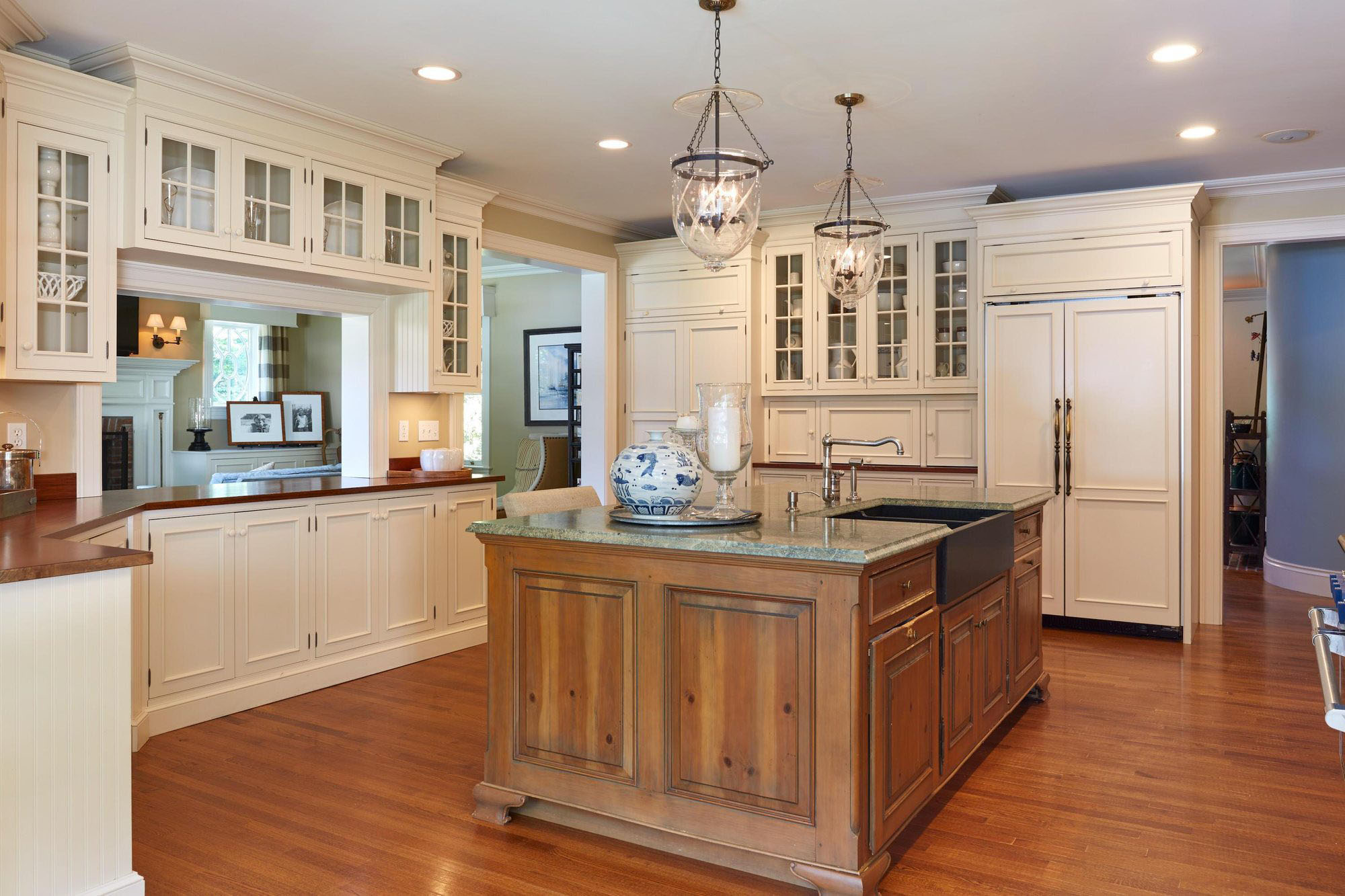 Country style kitchen with cream cabinets and stained wood island. granite countertops. stone sink.