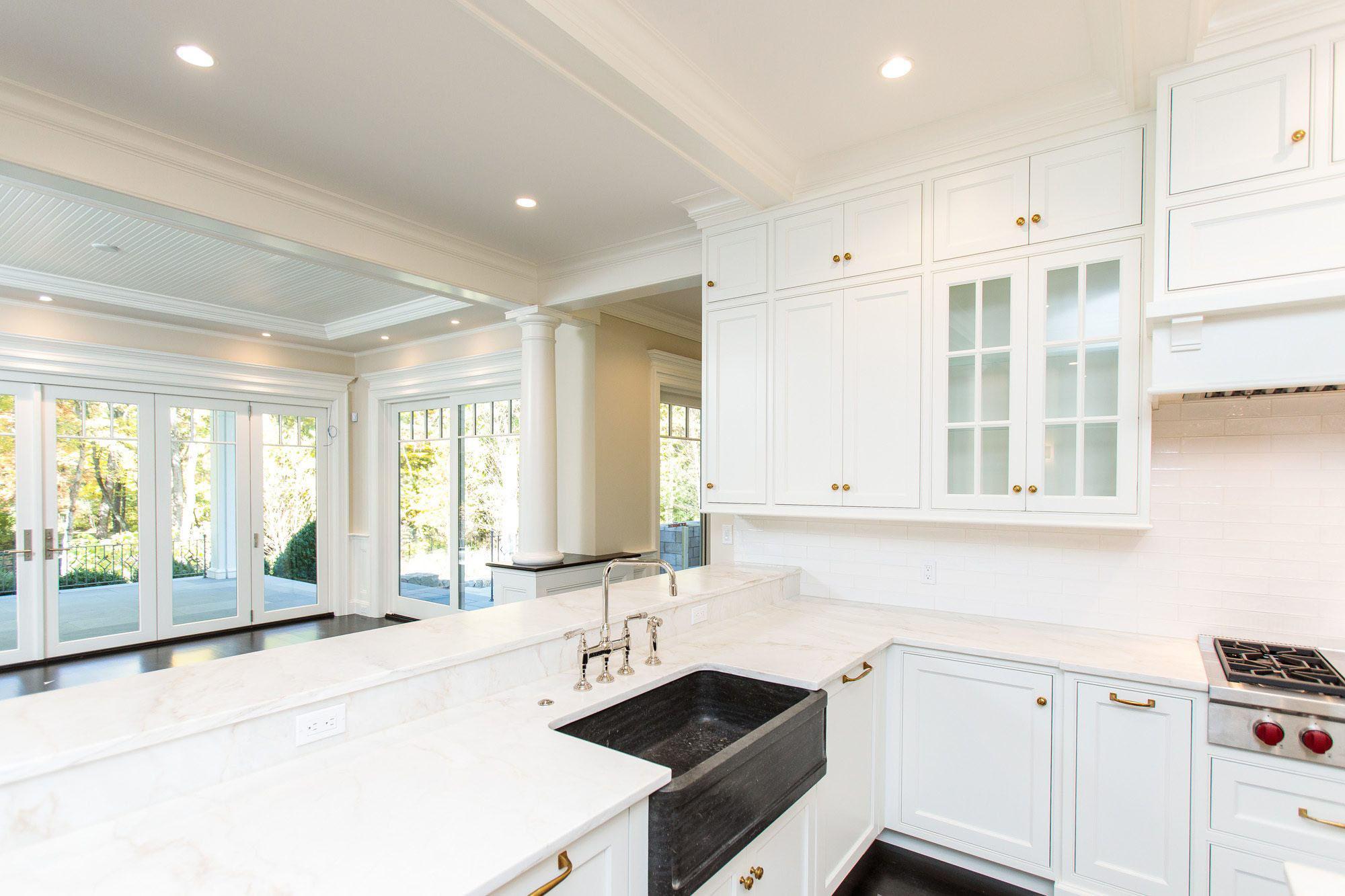 White kitchen with black stone farm house sink.