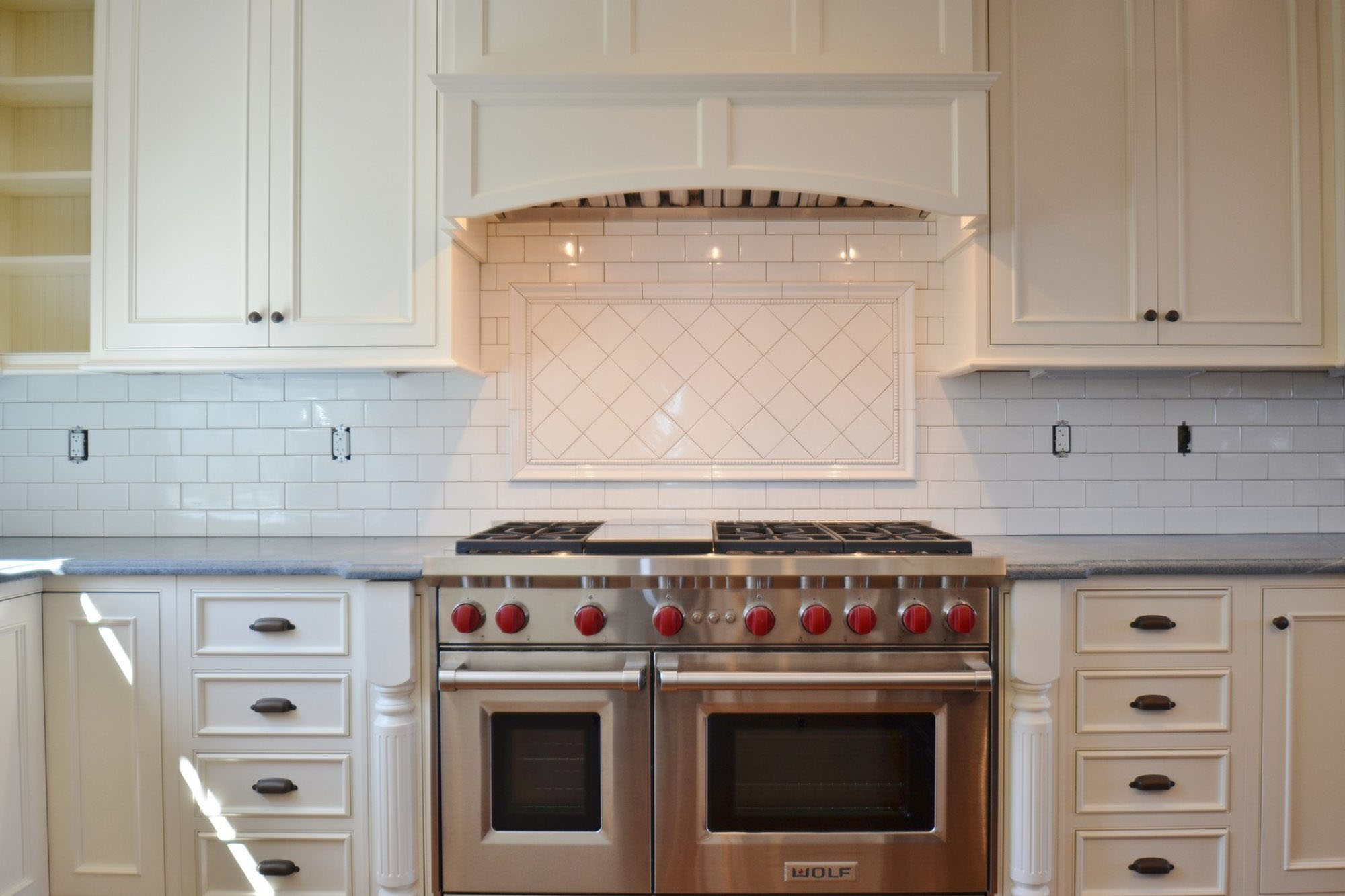"""Wolf 48"""" dual oven range with red knobs and 6 burners."""