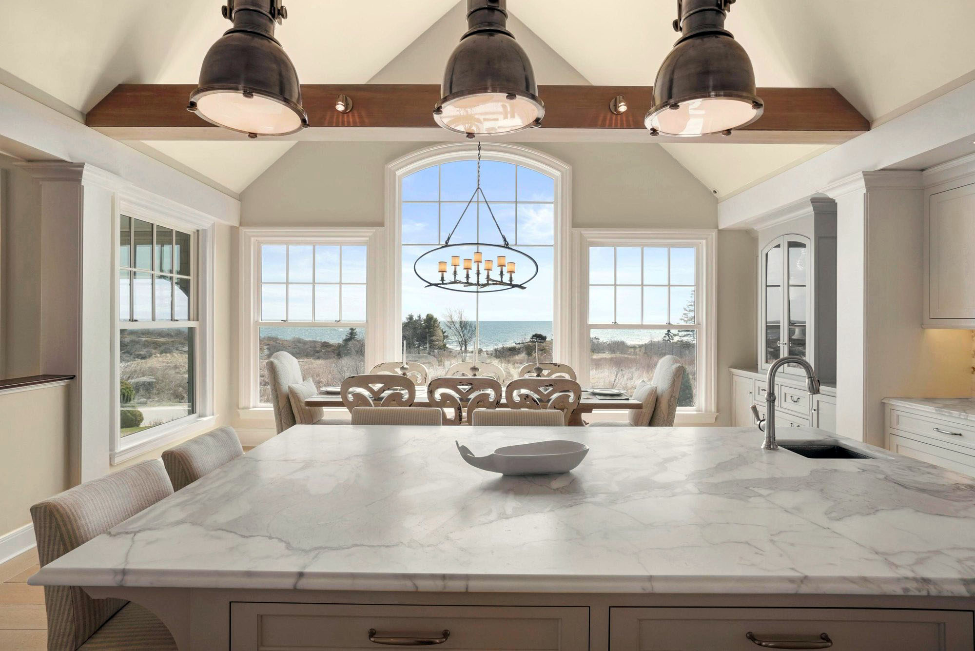Beautiful traditionally styled kitchen with an ocean view. Cream colored cabinetry with marble countertops, exposed wood beams and industrial pendant lighting.