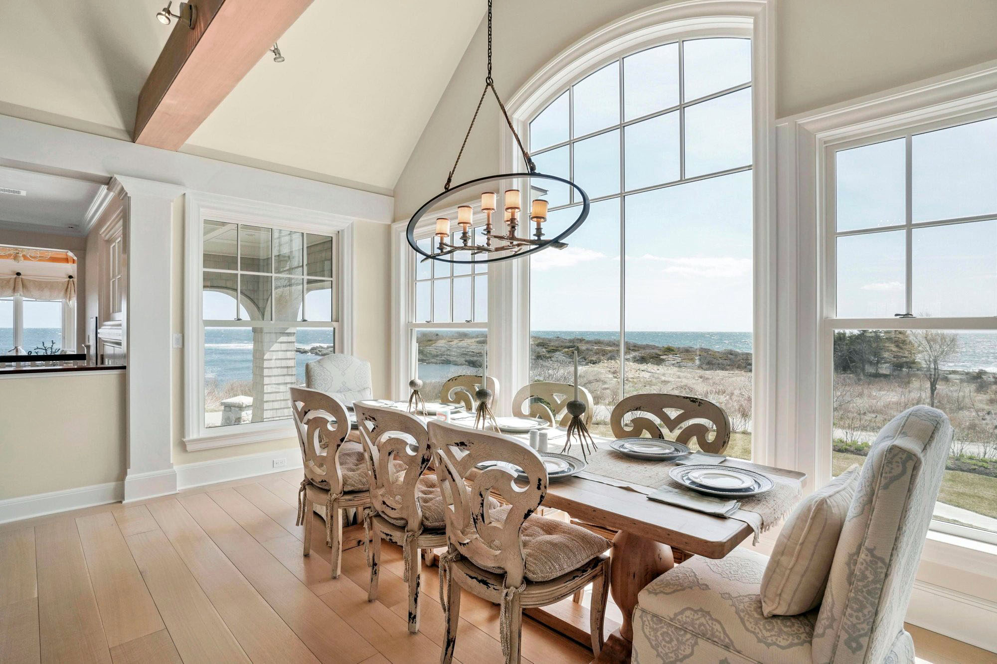 Spectacular ocean view from the 8 seat wood kitchen table. A mix of aged white washed and plush chairs.
