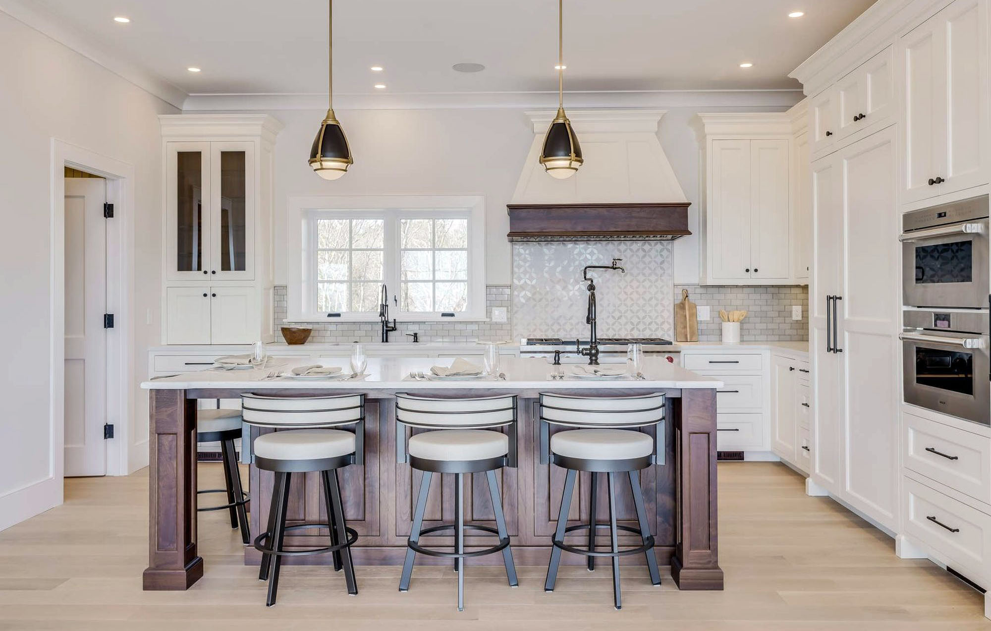 White shaker style kitchen cabinets with aged bronze knobs, light hardwood floors, stainless steel appliances and brown wood island.