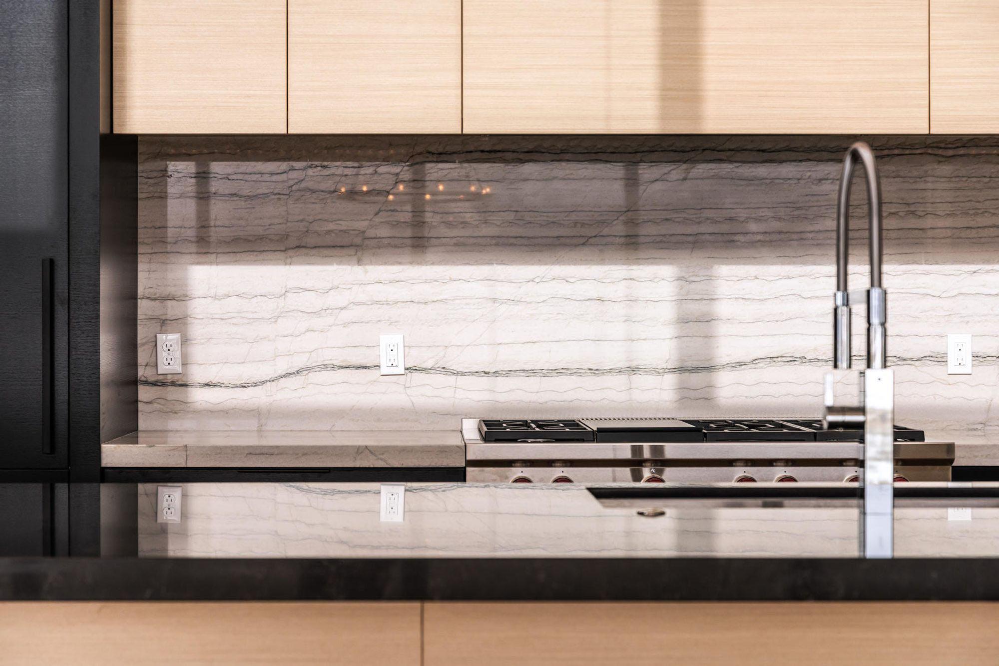 Ultra modern kitchen design with solid slab backsplash and flat faced cabinetry.
