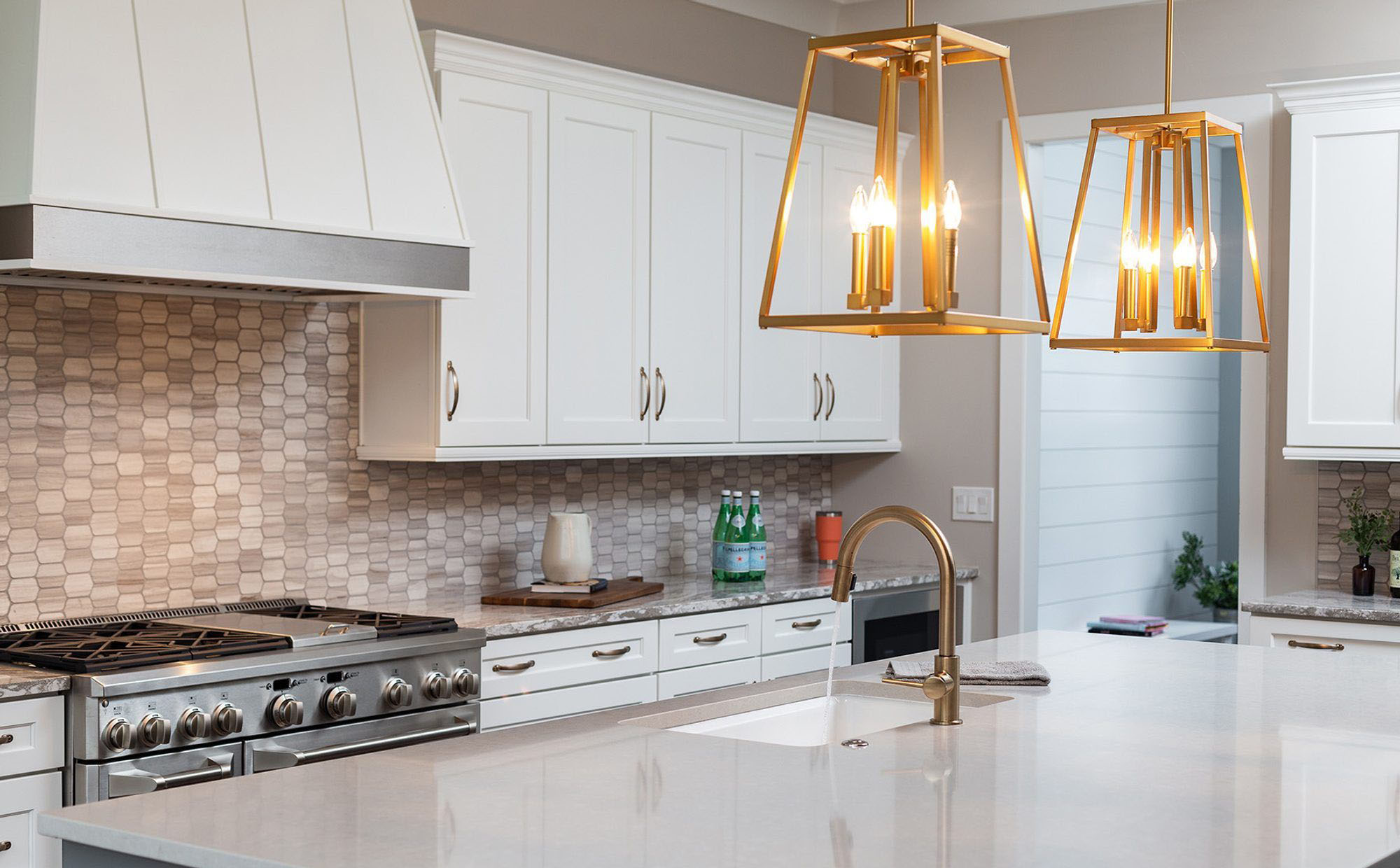 White kitchen cabinets with gold faucets, hardware and lighting.