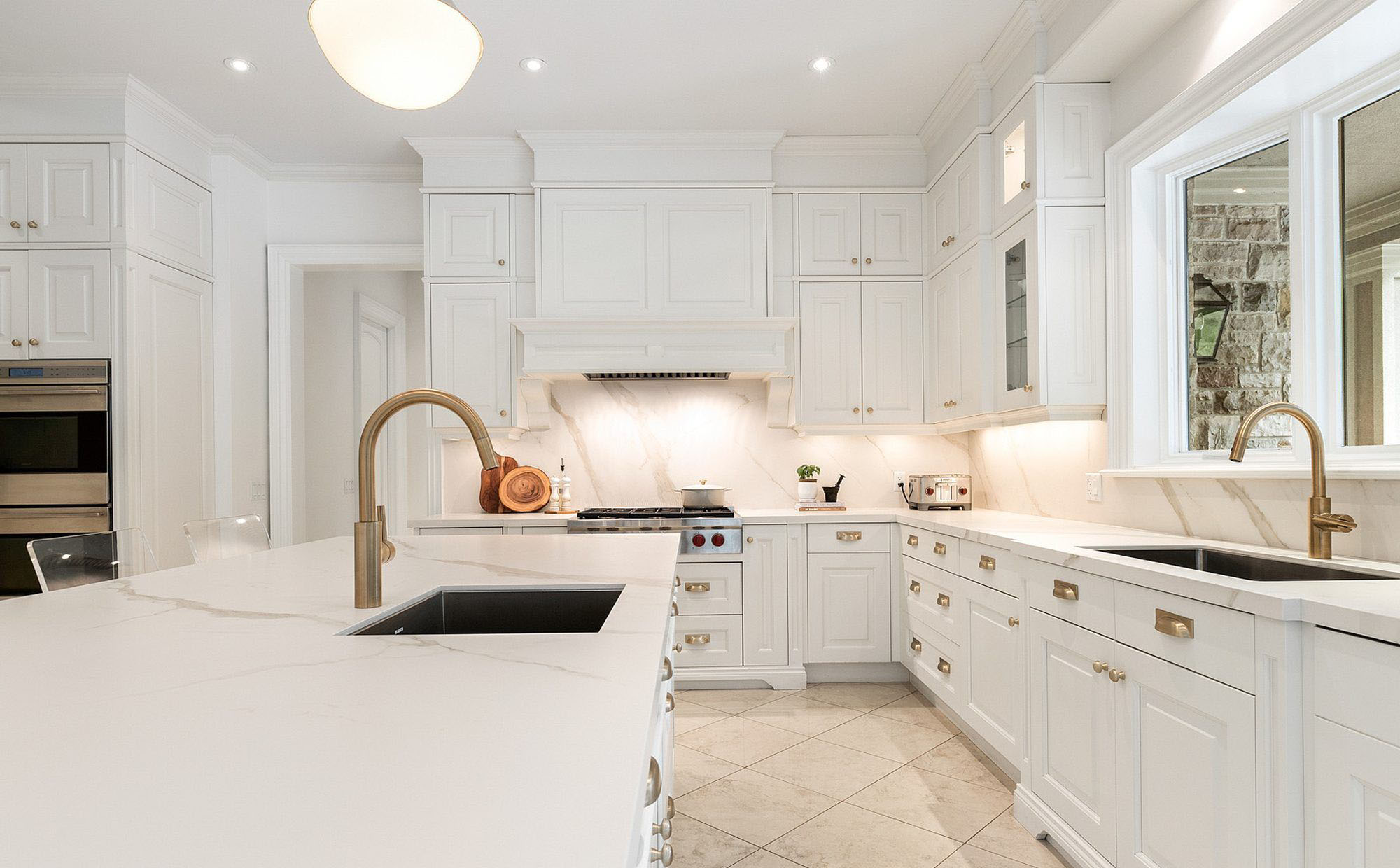 Fantastic luxury kitchen featuring white cabinets, solid slab quartz backsplash with matching counters, and gold hardware.