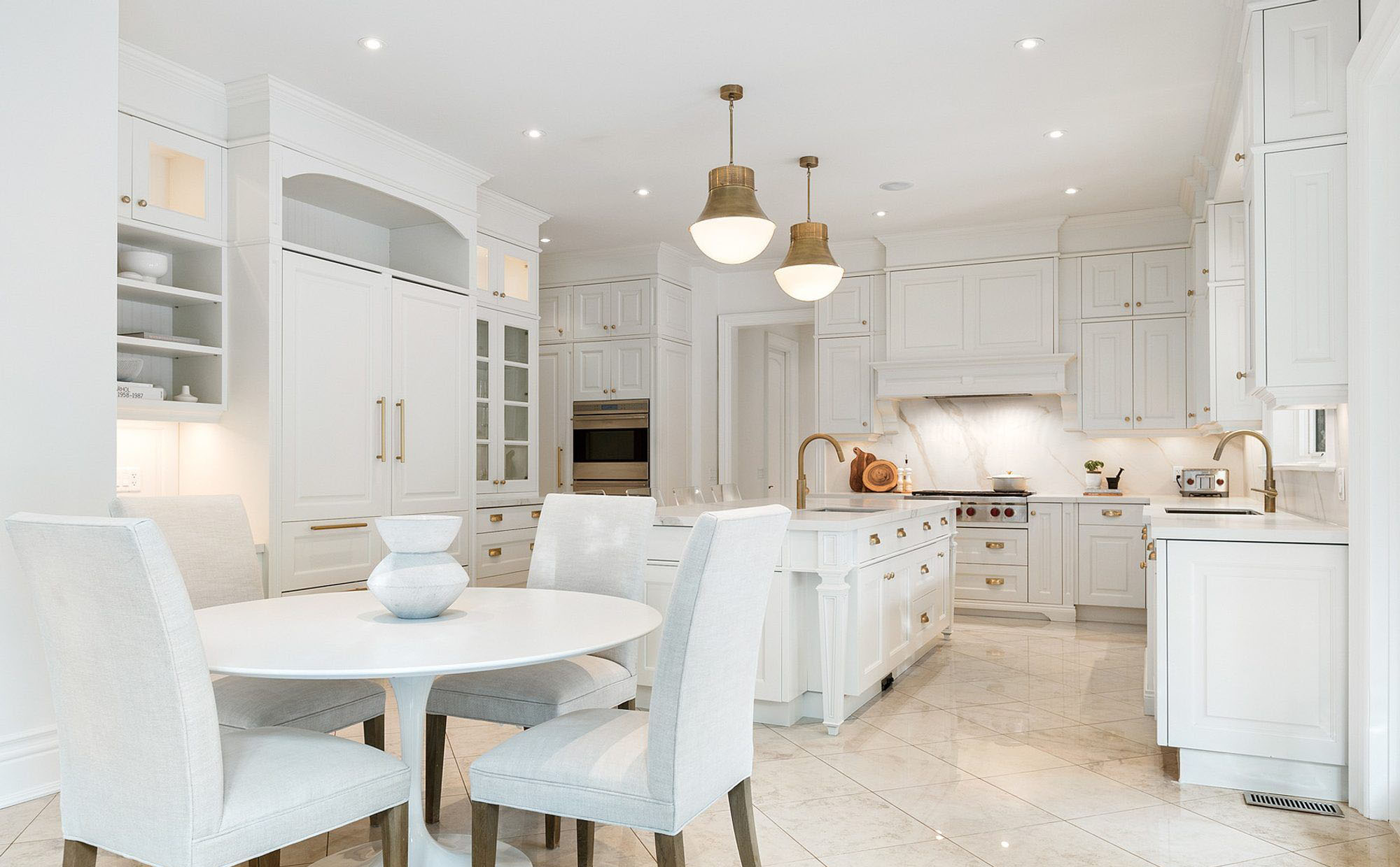 Beautiful luxury kitchen featuring white cabinets and matching island. Gold hardware, faucets and lighting.