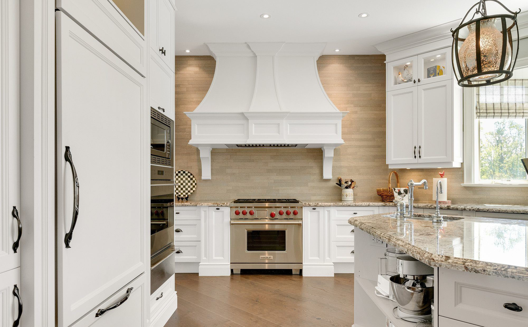 Tan stone feature wall with white cabinets and a matching range hood. white kitchen cabinet ideas.