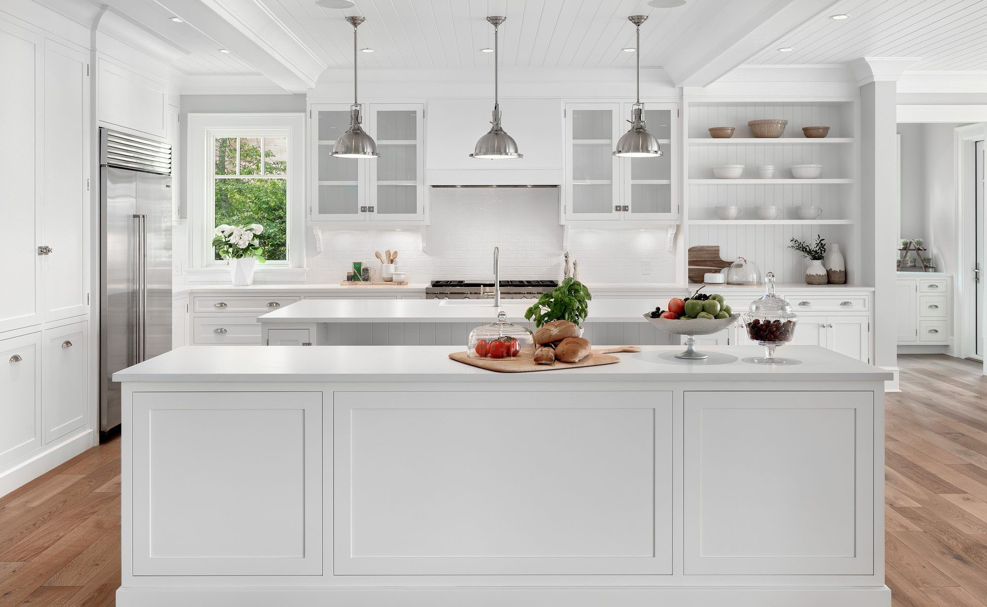 White kitchen cabinets with a cool undertone and a modern feel. Two matching white islands. white kitchen cabinet ideas.