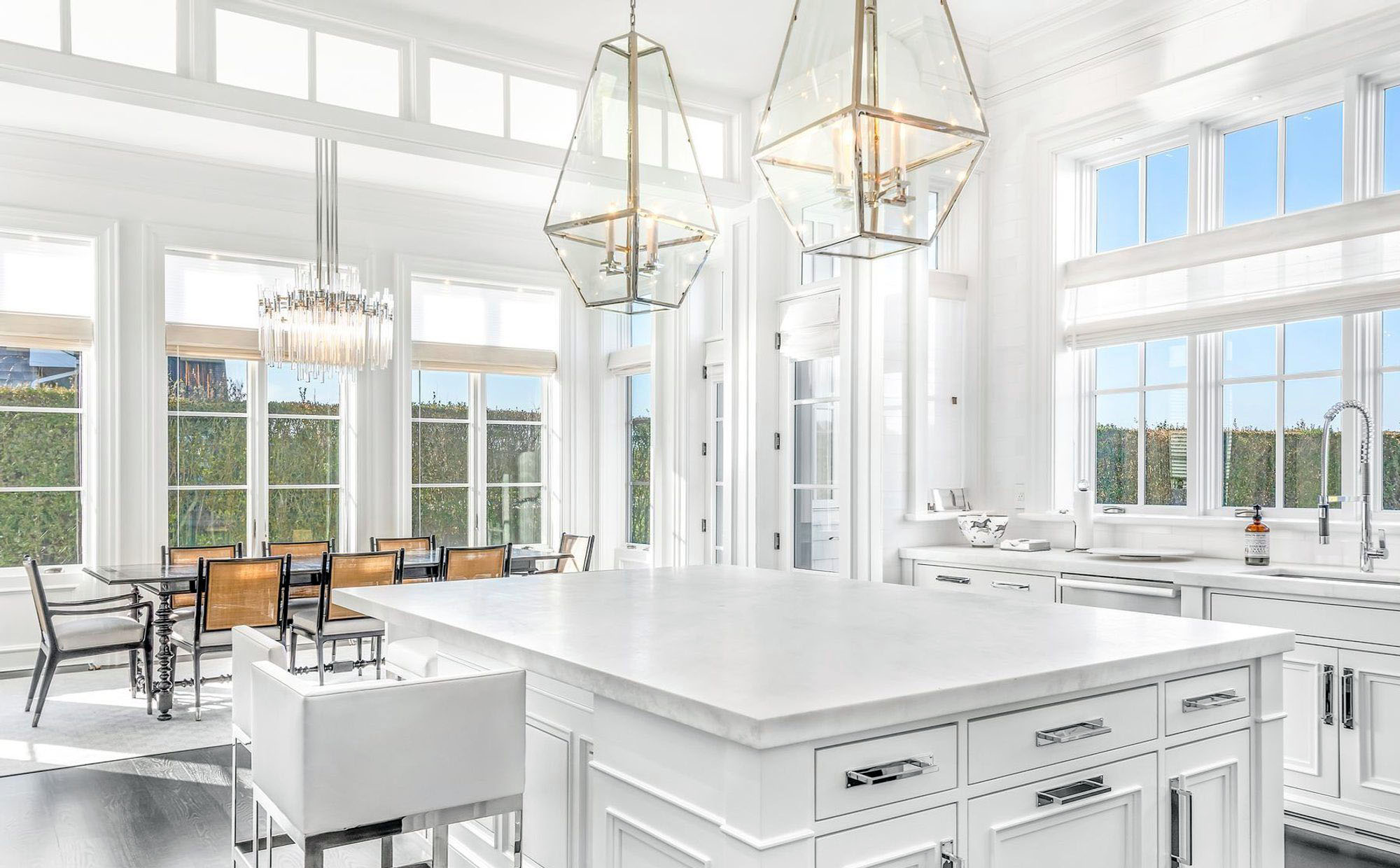 All white home with white cabinets, chrome hardware and matching faucets.