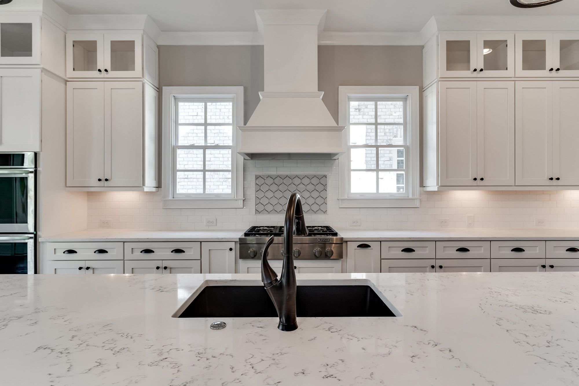 All white kitchen design featuring white shaker style modern cabinets, white subway tile backsplash and black hardware.