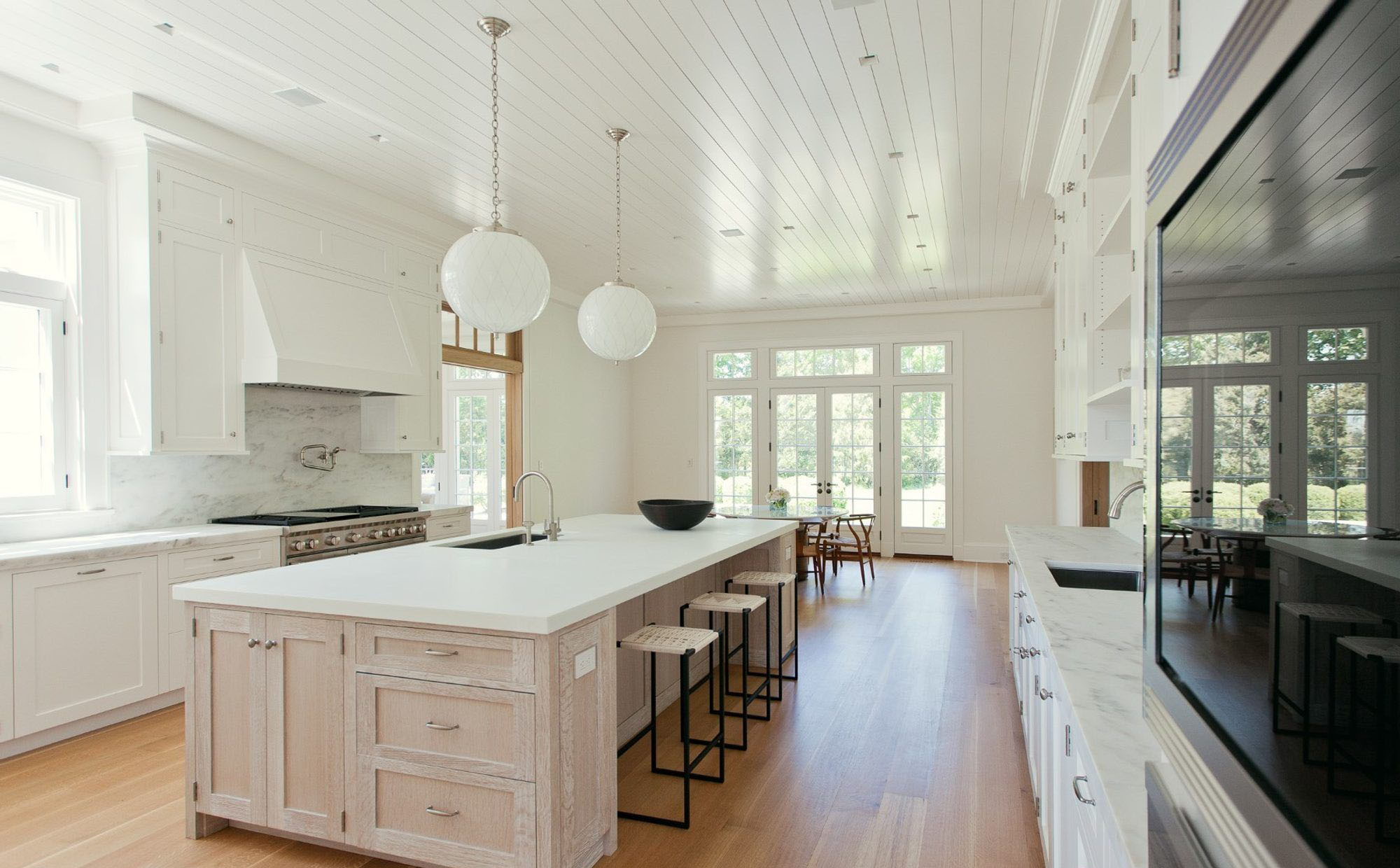 Pale light wood custom built island with hardwood floors and pure white cabinets.