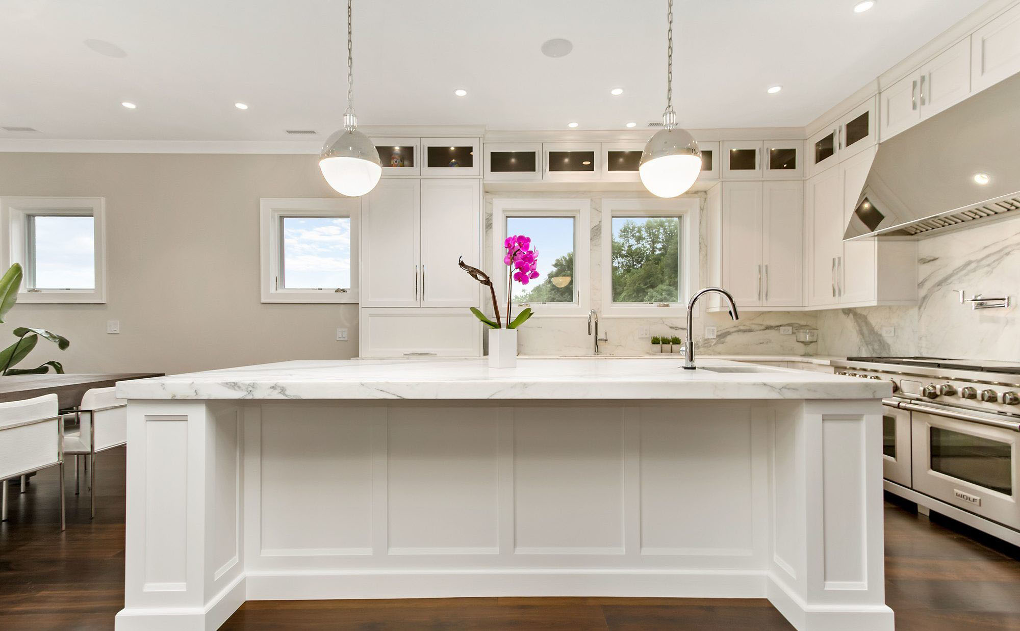 White kitchen cabinets run all the way to the ceiling with small glass face uppers.
