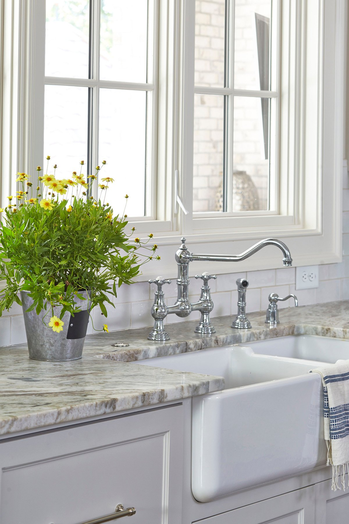 White cabinetry with a white farmhouse sink.