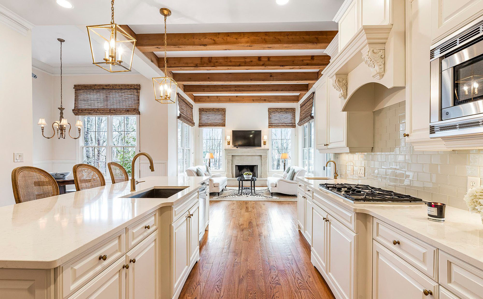 Traditional style kitchen using warm cream cabinets, hardwood floors and exposed ceiling beams.