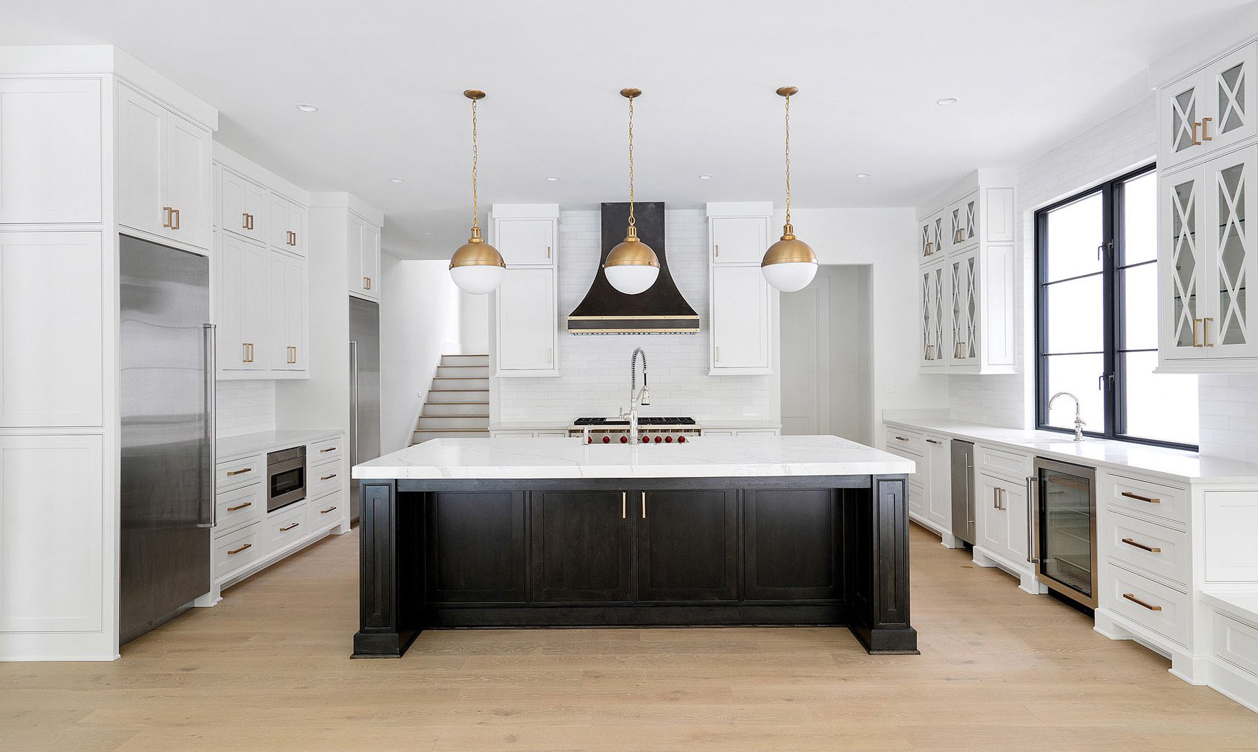 Two tone kitchen cabinets featuring white uppers and lowers with a black center island.