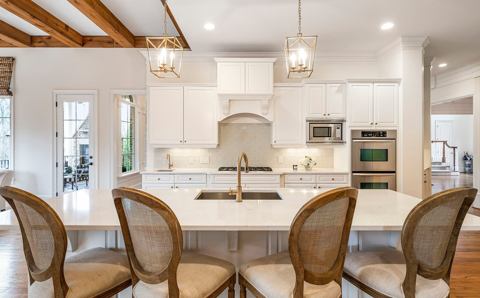 Beautiful white kitchen cabinets with a matching white island, white walls and white glass backsplash.