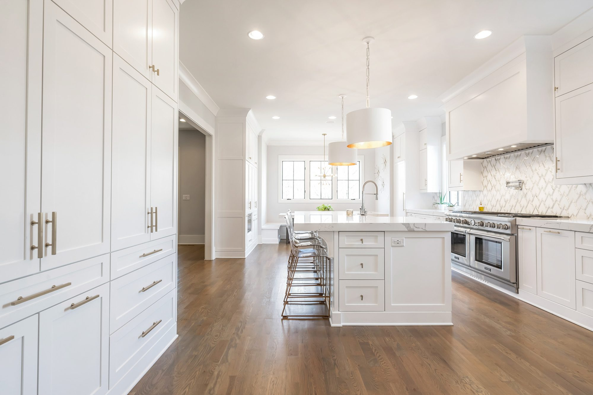 White kitchen cabinets with matching white backsplash, countertops and lighting.