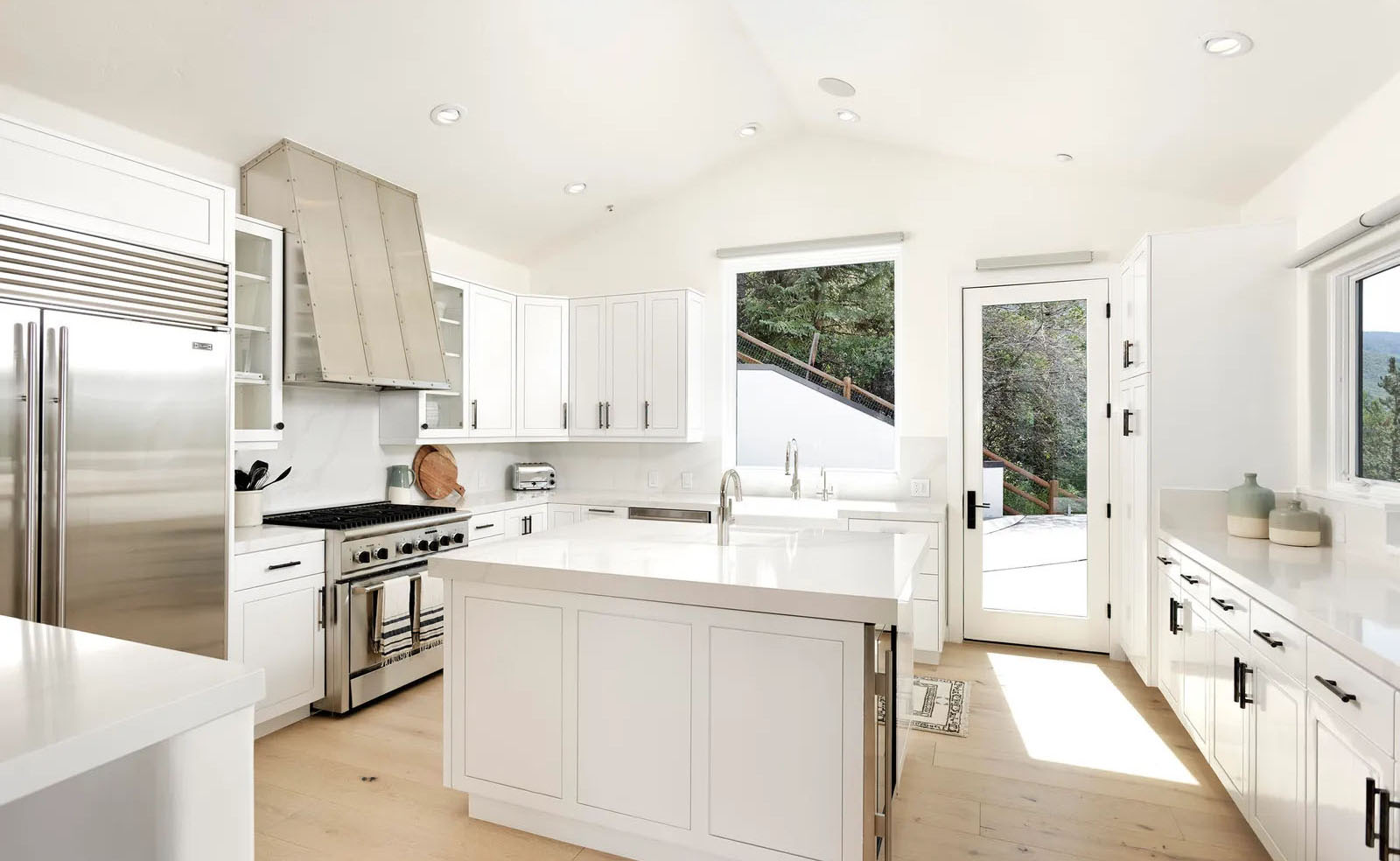 White kitchen cabinets with a custom made range hood.