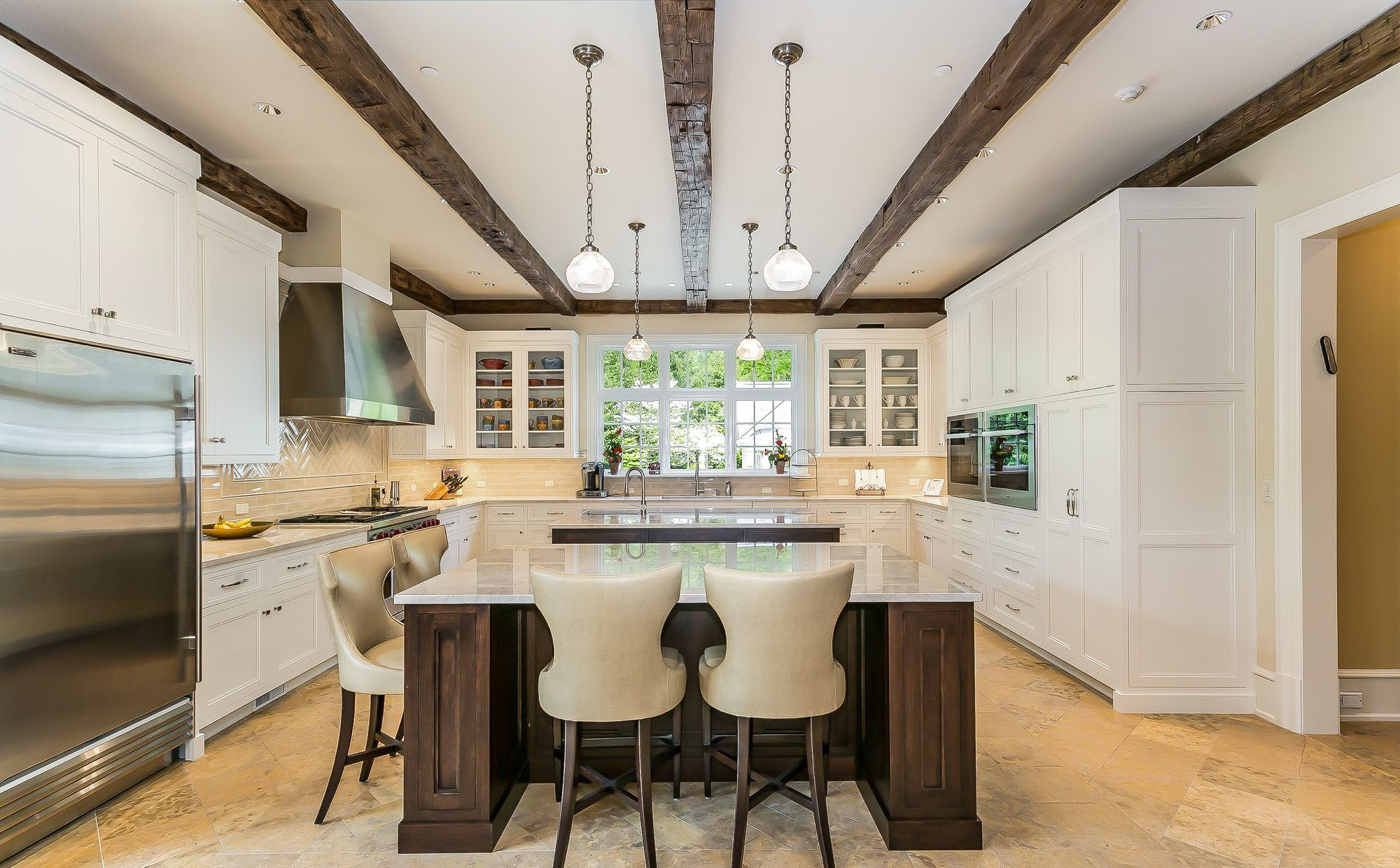 Traditional style kitchen featuring white cabinets, exposed wood ceiling beams and a wood island. white kitchen cabinet ideas.