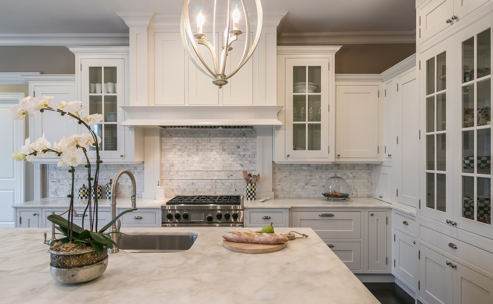 Beautiful luxury kitchen with marble countertops and backsplash with medium gray grout.
