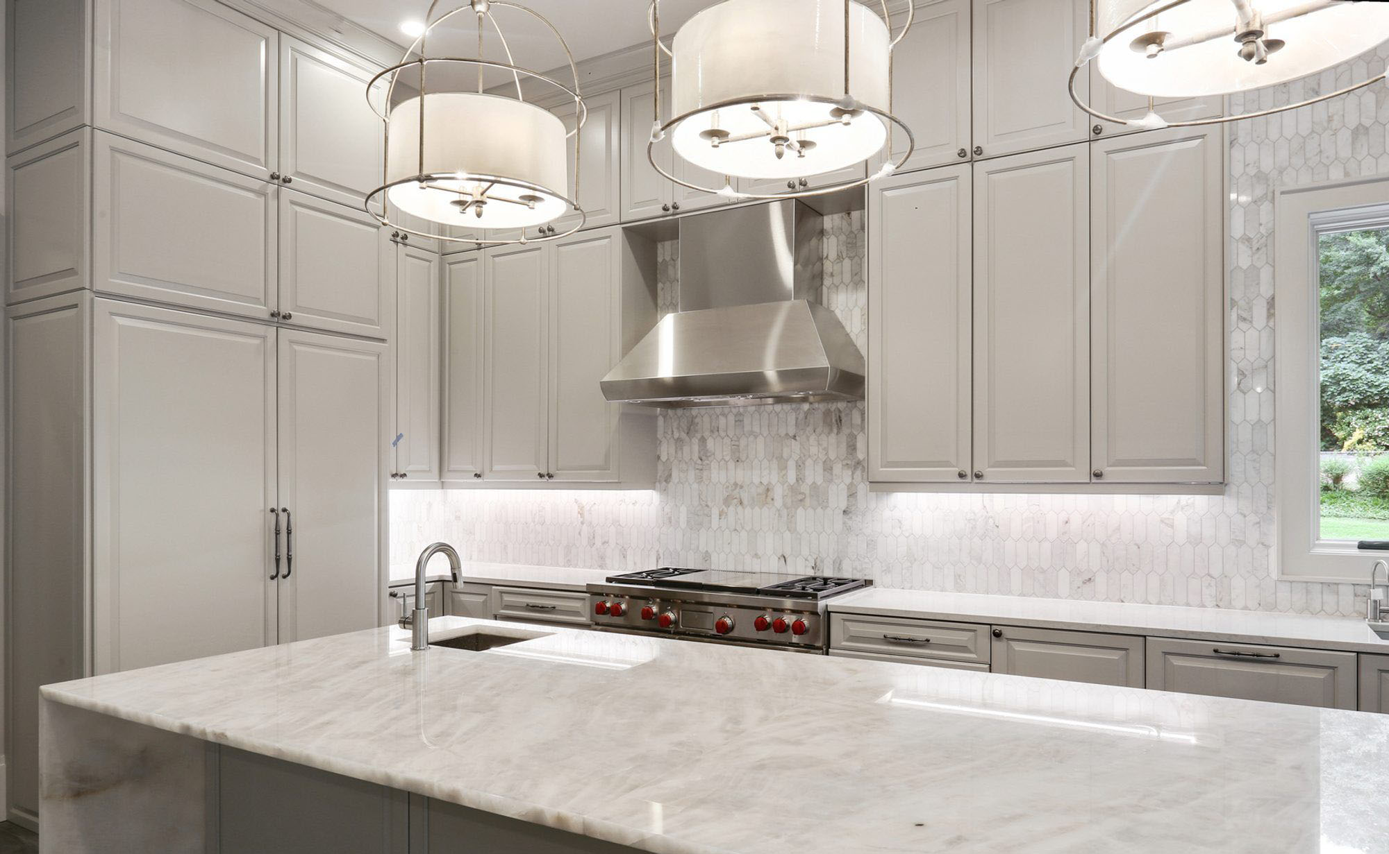 Gray kitchen using marble tile backsplash and countertop, soft gray cabinets, stainless steel appliances and light gray grout.