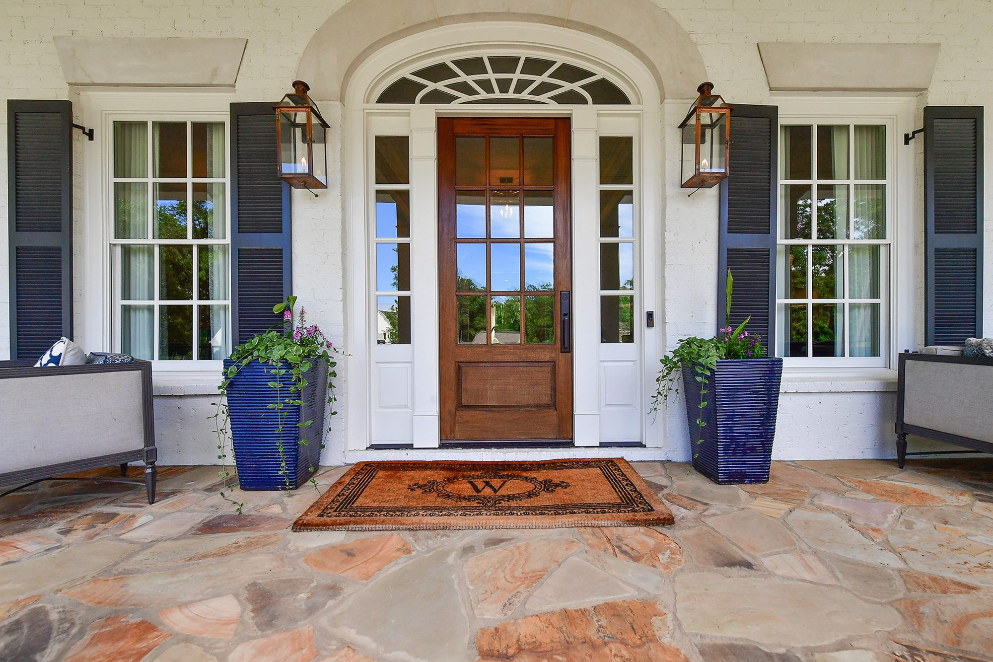 Closeup view of the stained wood front door and painted white brick walls. how to paint brick.