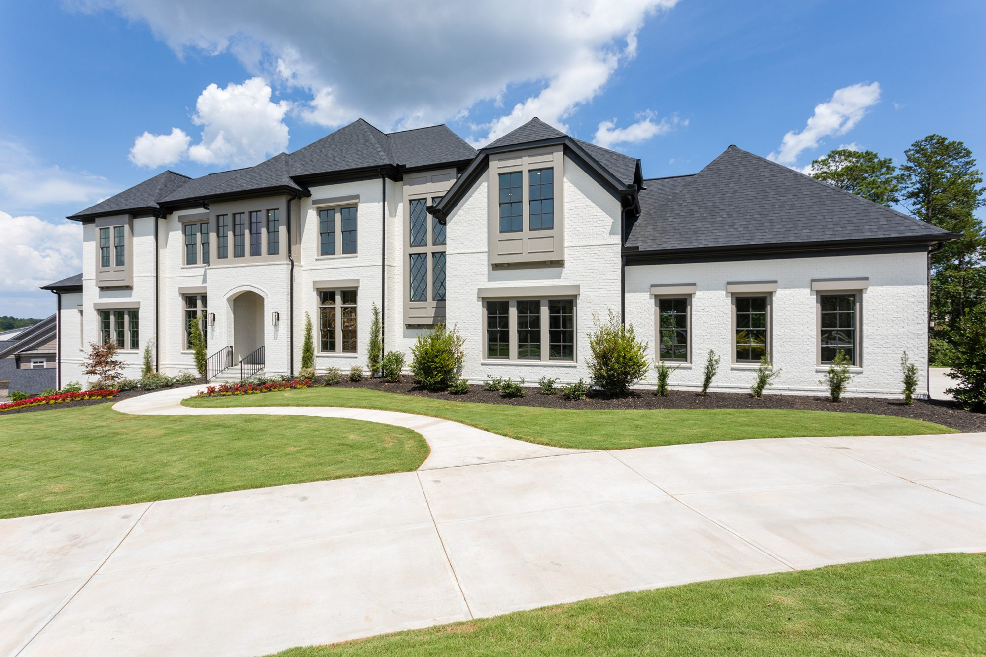 Modern style new home with painted white brick siding.