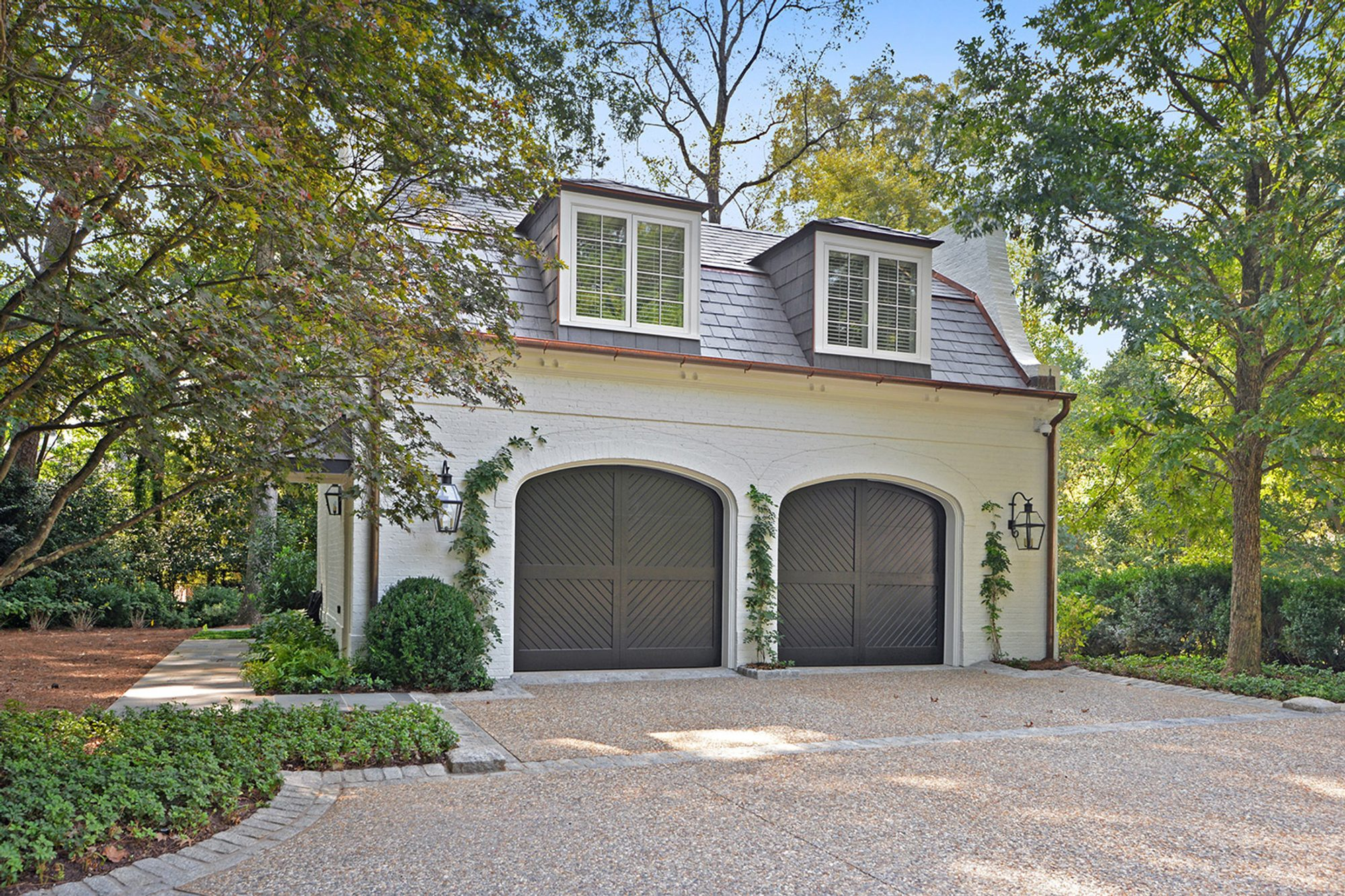 Painted white brick detached garage with black doors.