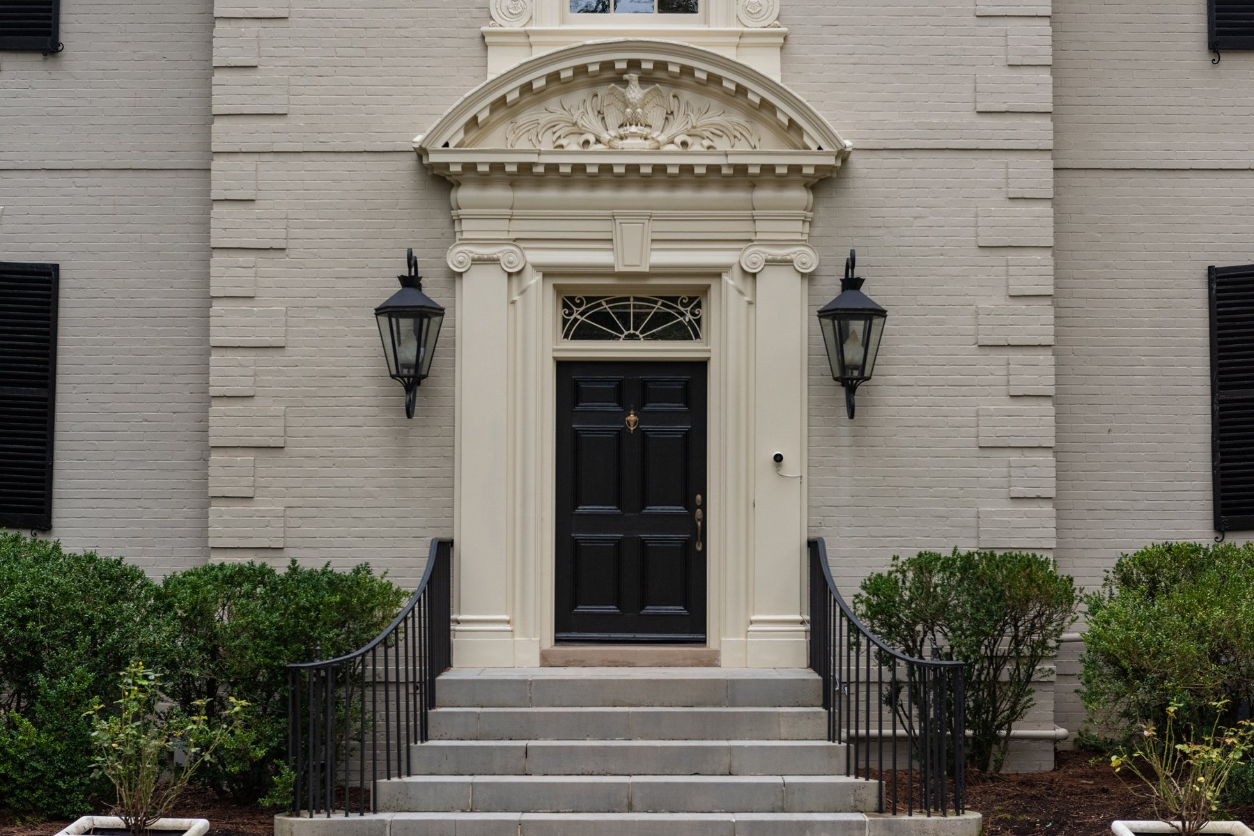 A closeup view of the black front door, elaborate trim surround and masonry steps with black iron railings.