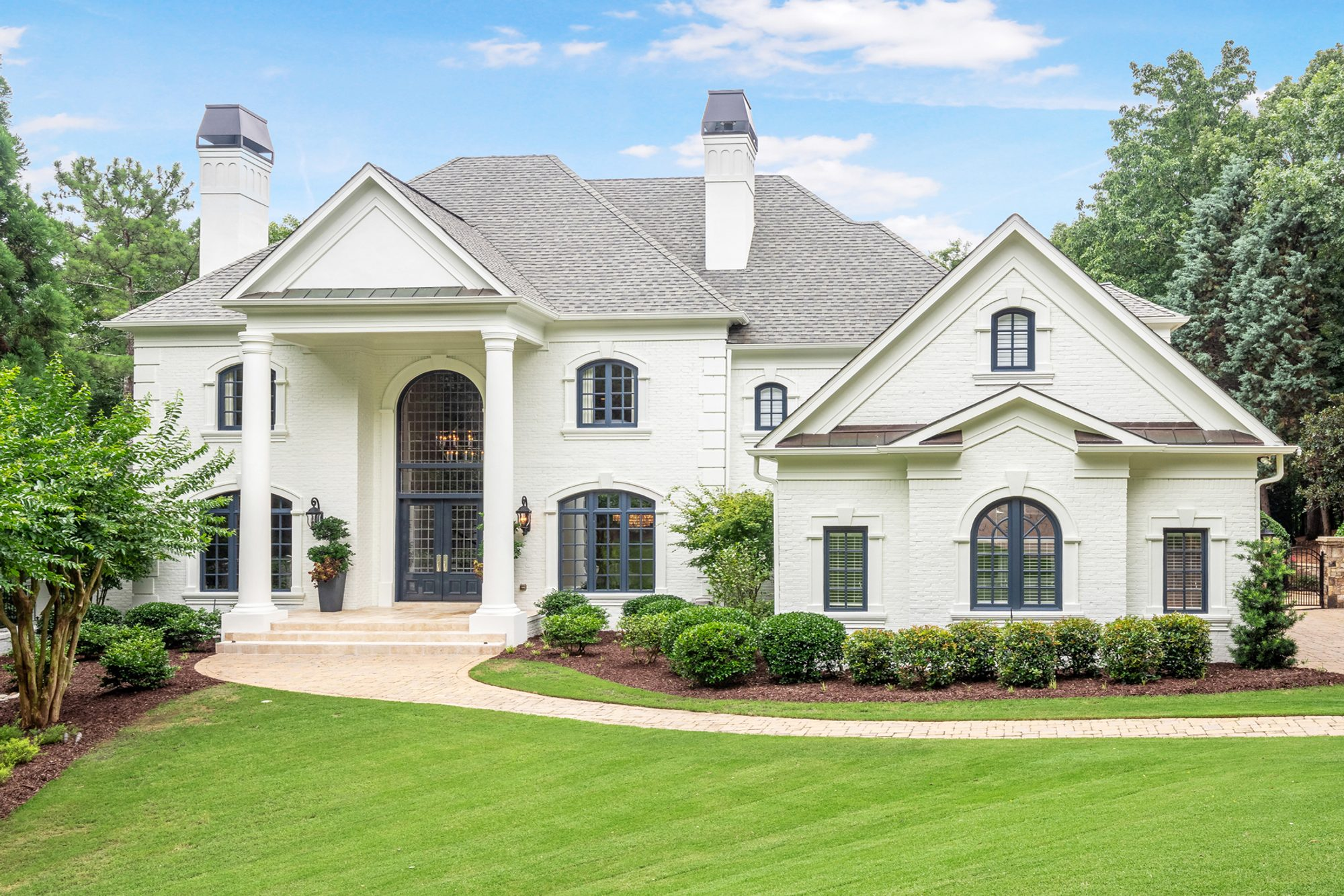 Traditional style red brick home painted white with blue trim and huge columns.