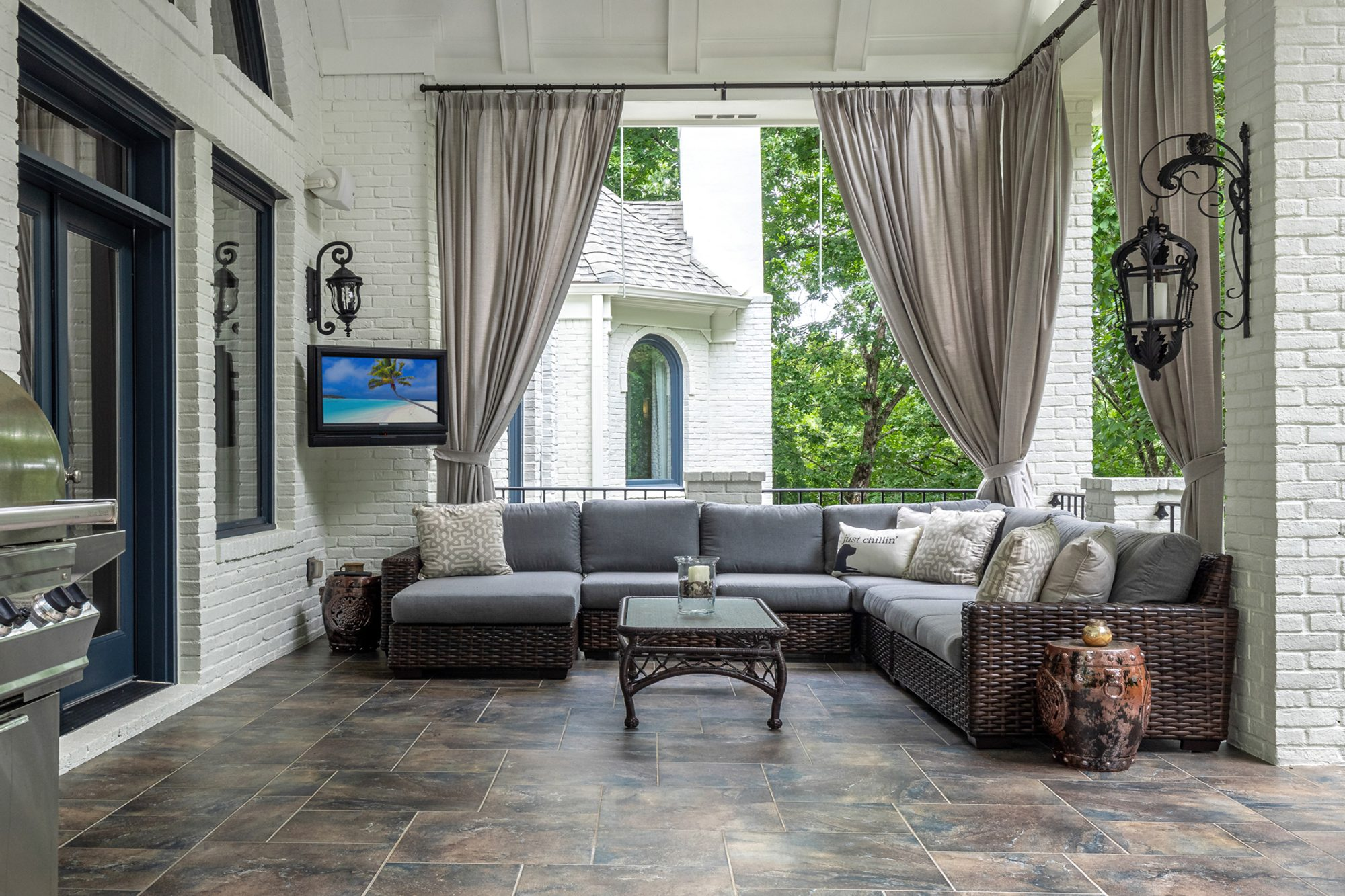 Back covered porch with painted white brick walls and columns.