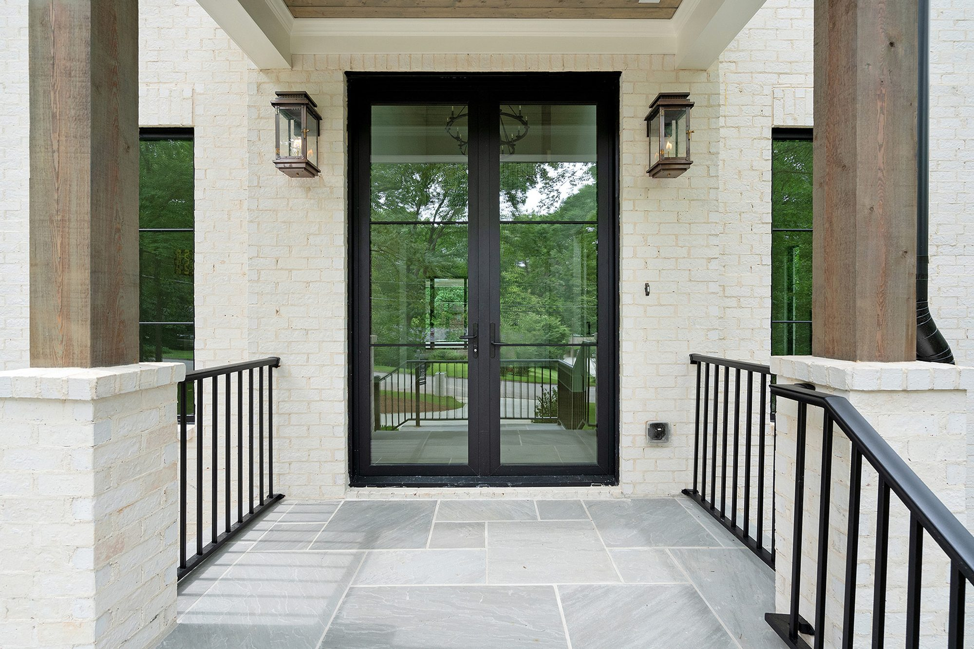 Closeup view of the Modern style black front door with painted white brick siding.