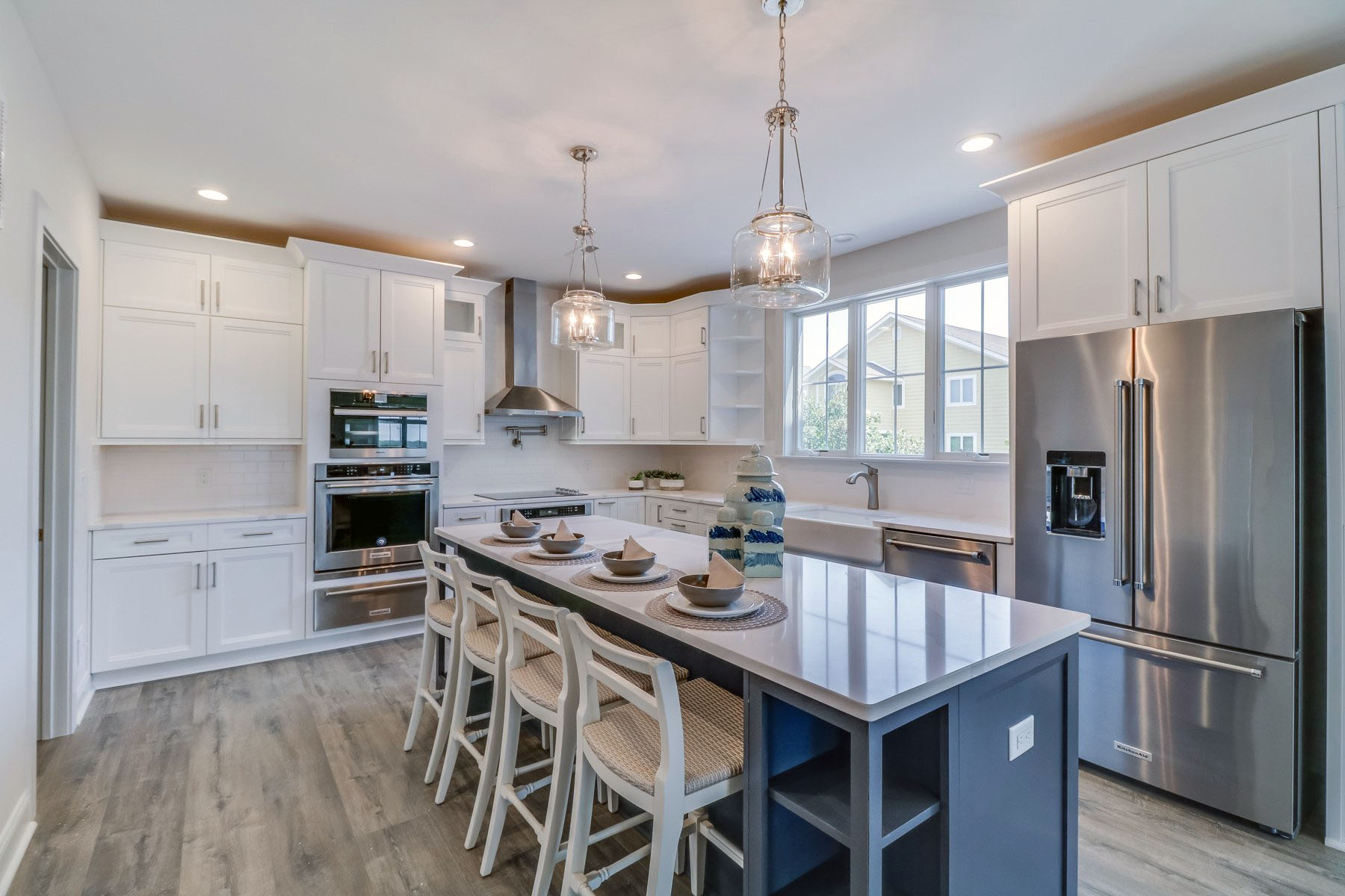 Gray blue island with white shaker style cabinetry. Muted gray faux wood floors.