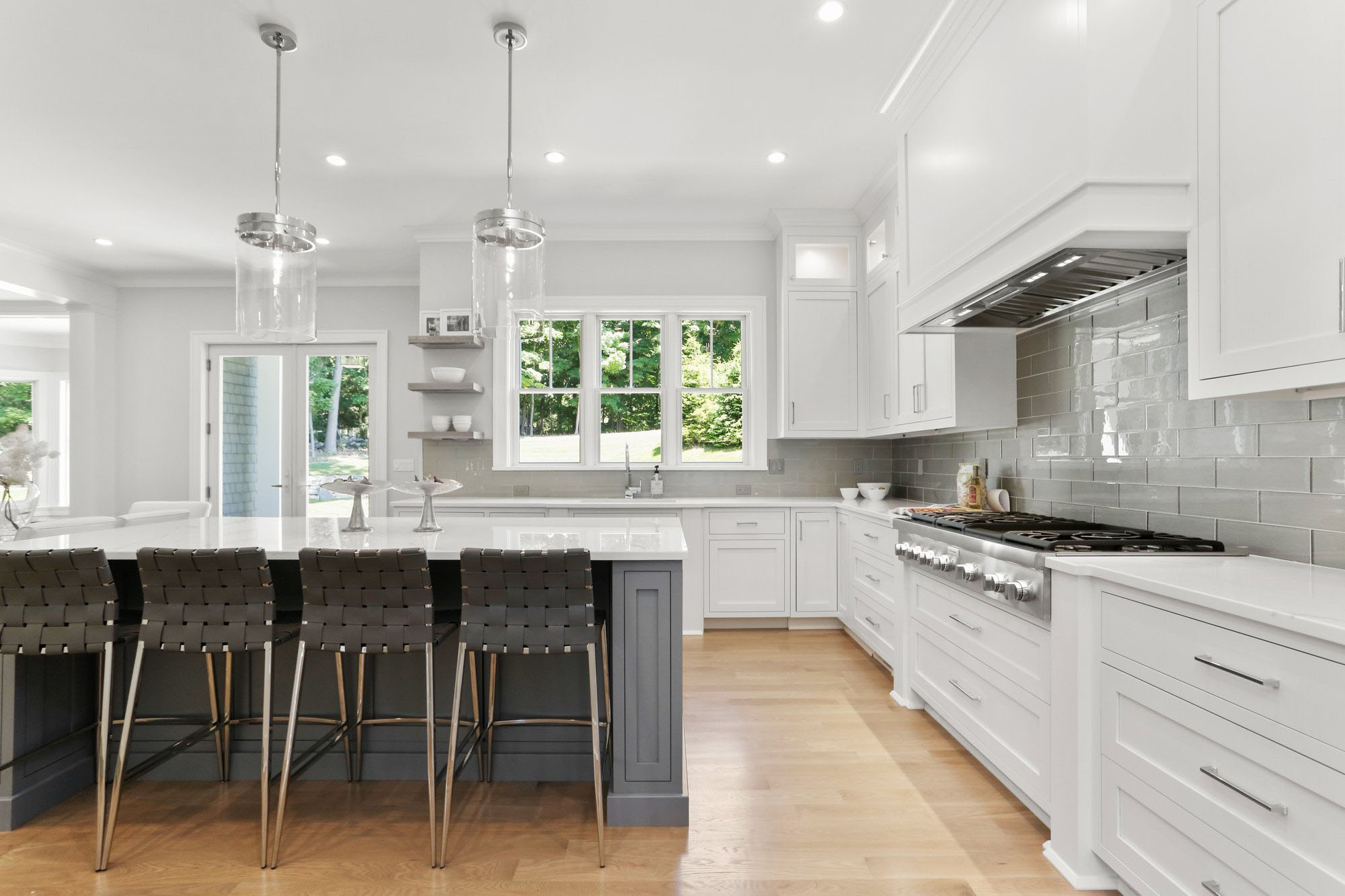 White shaker style cabinets with a medium gray island. Gray glass tile backsplash with marble quartz countertop.