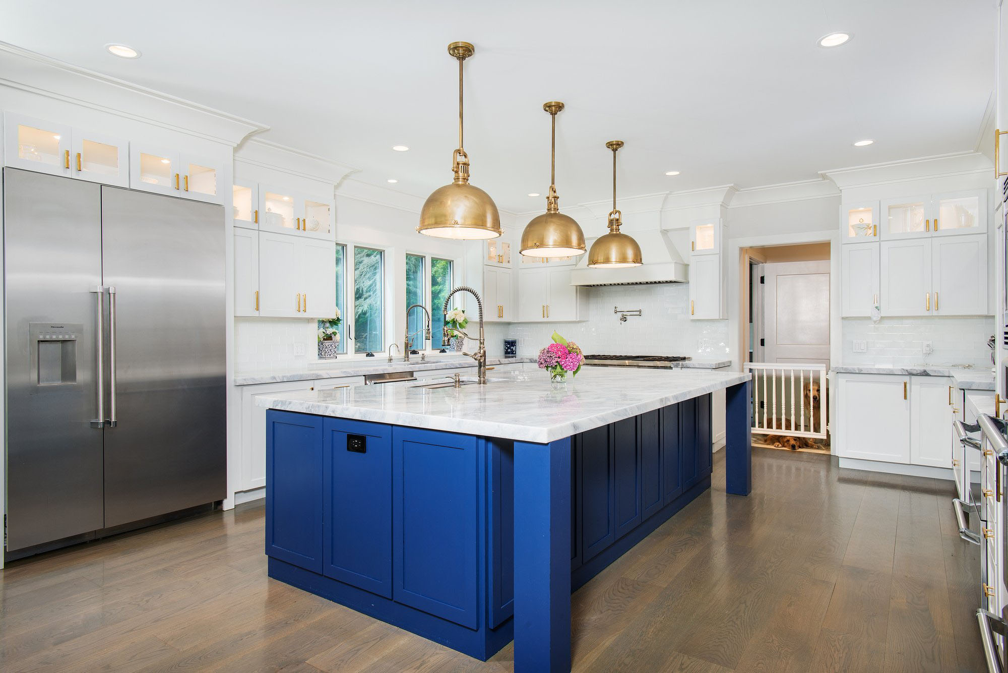 Bright blue island with white shaker style cabinets. Two kitchen cabinet colors brought together by matching marble countertops and gold hardware.