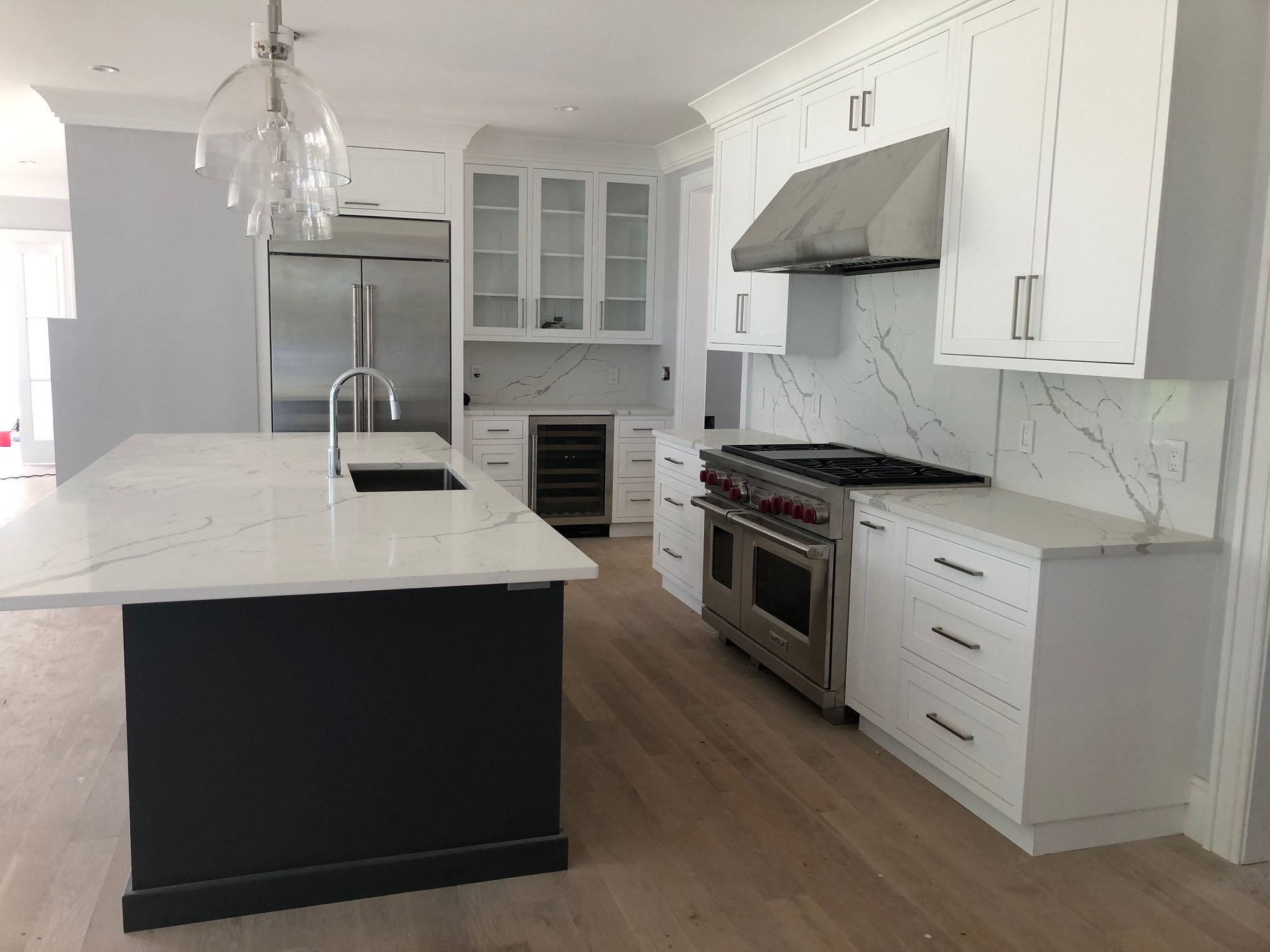 Two toned kitchen cabinet design featuring white cabinets and a black island. Marble quartz countertops with matching solid slab backsplash.