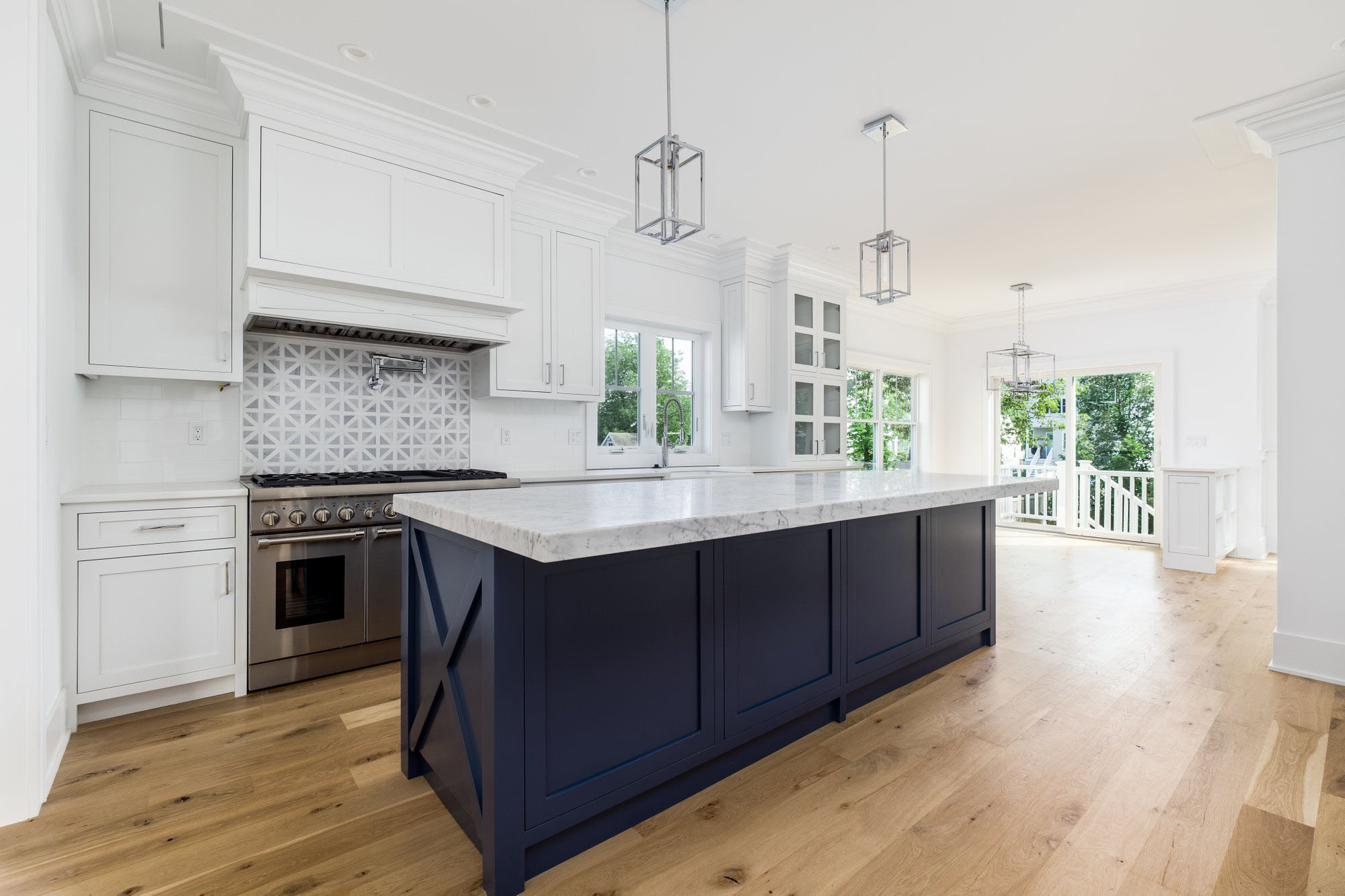 Two tone kitchen cabinets featuring white shaker style uppers and lowers with a dark blue island.