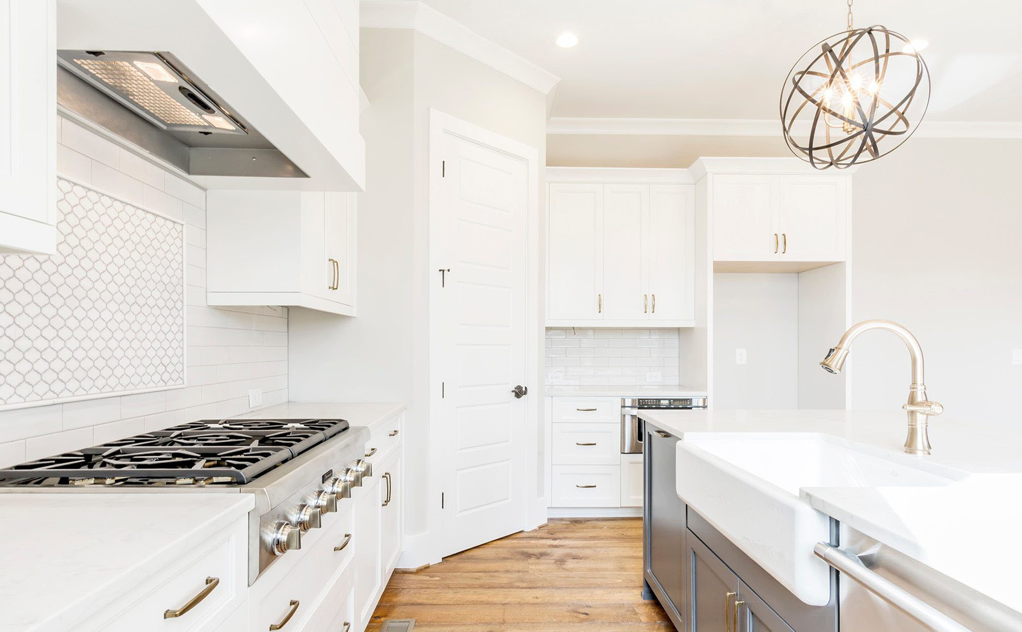 White kitchen cabinets paired with a medium gray island. Matching pale gold hardware.