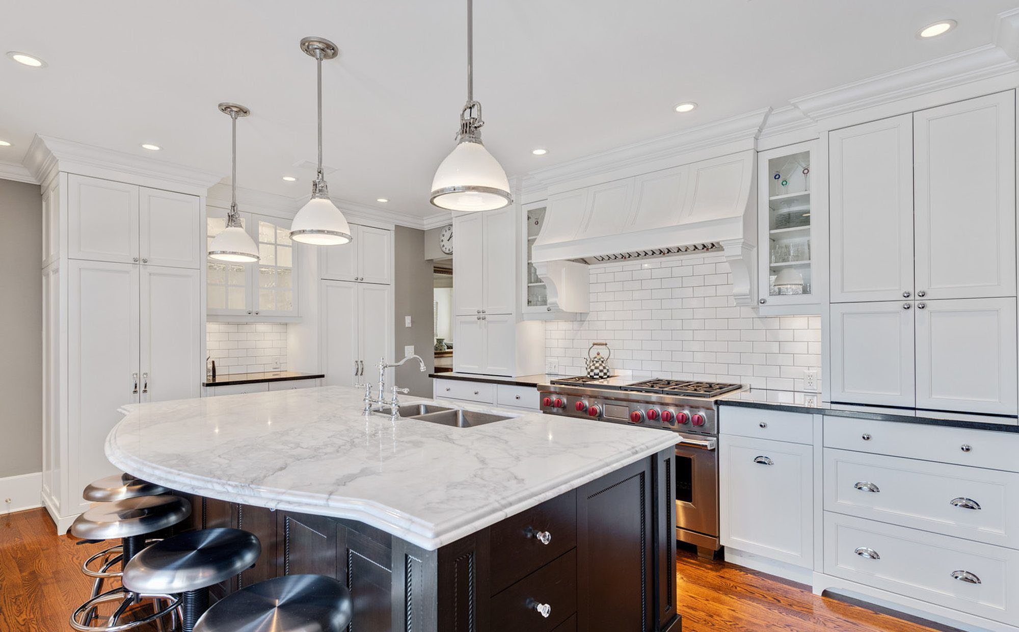 Multi colored kitchen cabinets. White shaker with a dark brown island.